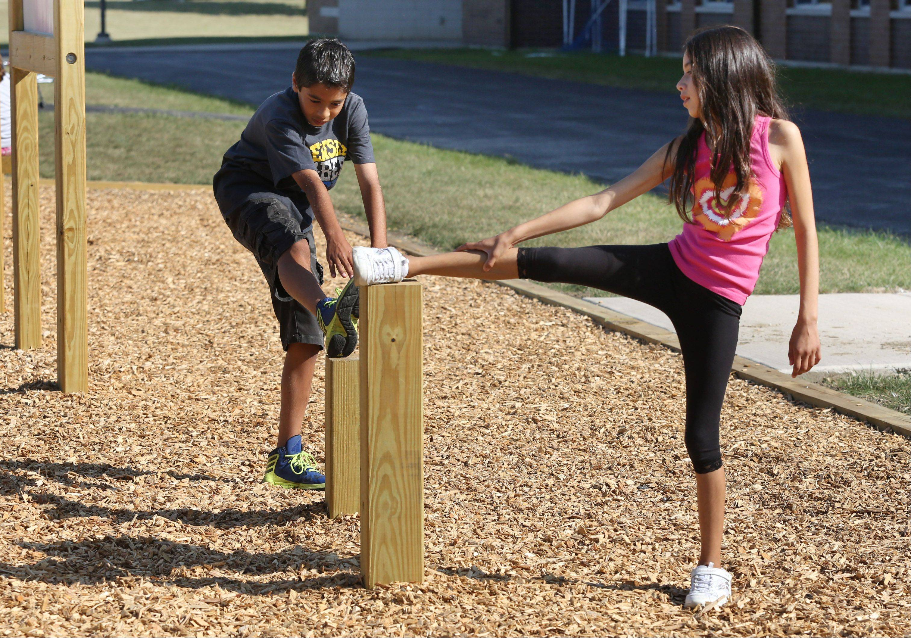Fifth-graders Gabby Colin and Ishaan Shah stretch on the new Fit-Trail station at Woodland Intermediate School in Gurnee. The new fitness station will be used for students during the school day and available to the community after school hours.