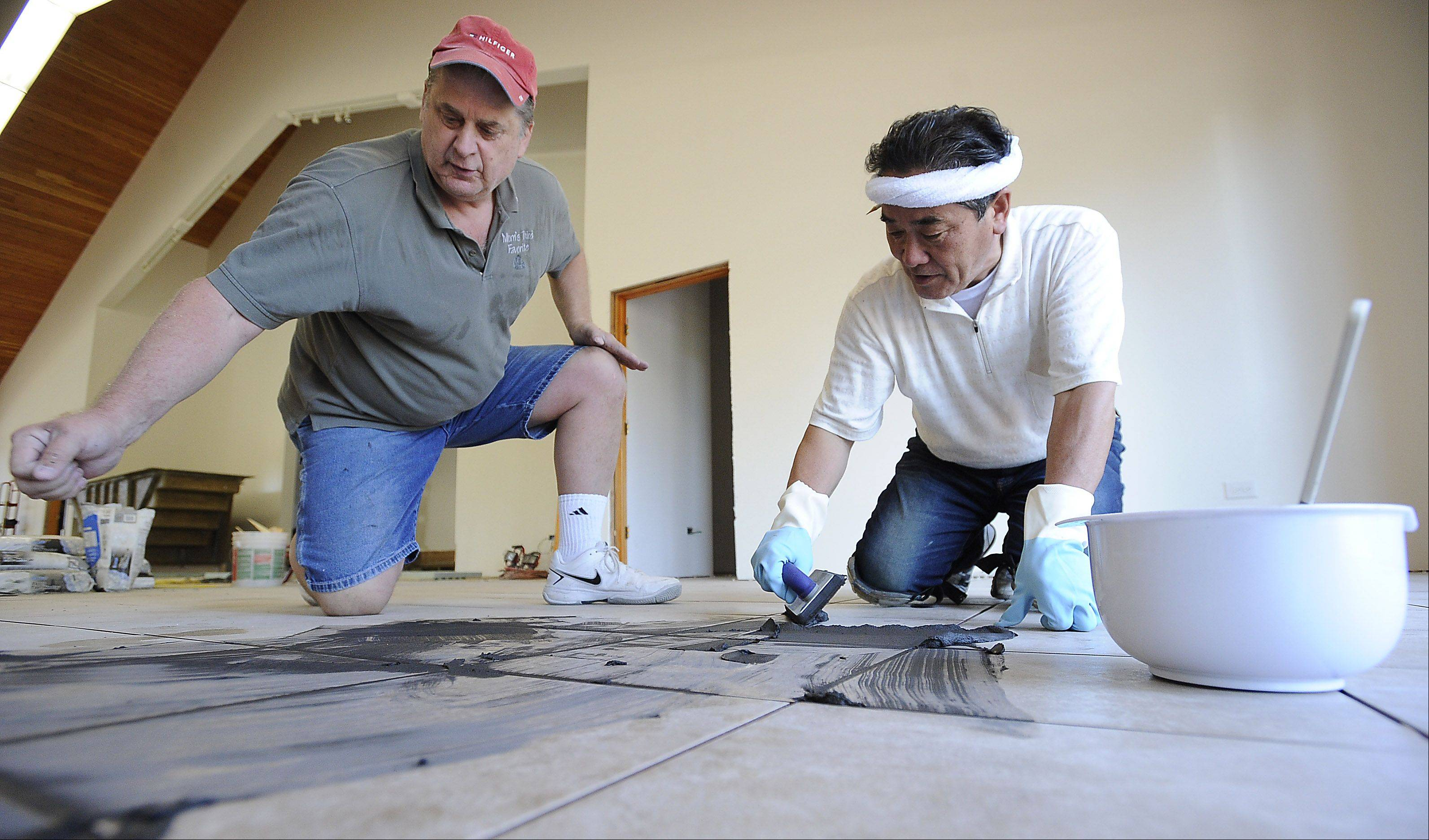 Rich Meyer of Mount Prospect shows Takahiro Tsutsui how he grouts the tile floor at the Chicago Japanese Mission Church in Arlington Heights. Tsutsui flew in from his native Japan recently to assist with the church's construction.