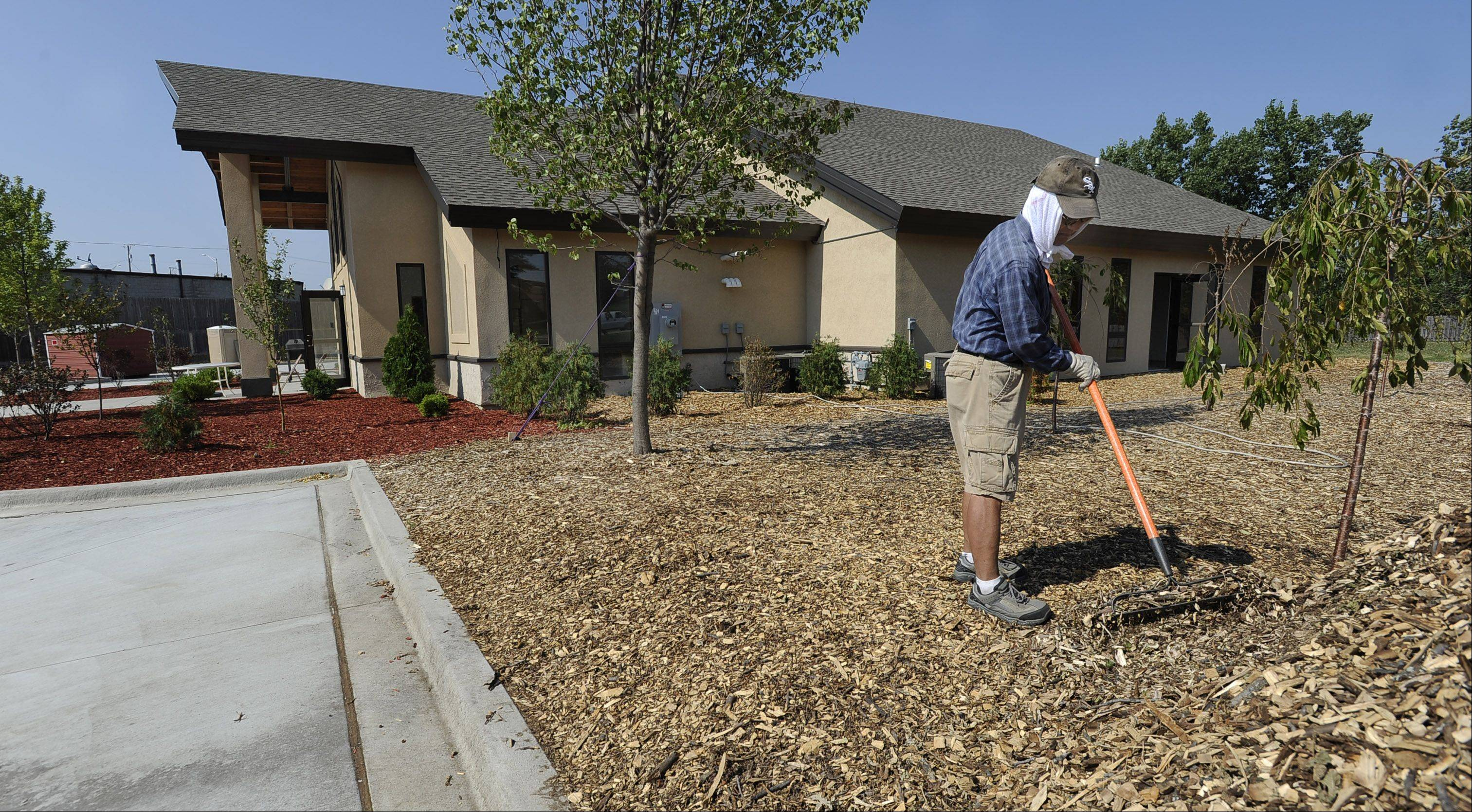 Mic Miyamoto of Buffalo Grove, a member of the Chicago Japanese Mission Church in Arlington Heights, spreads mulch around the church. He's one of many volunteers who are bringing the church closer to finally opening late this year after a three-year effort to build it.