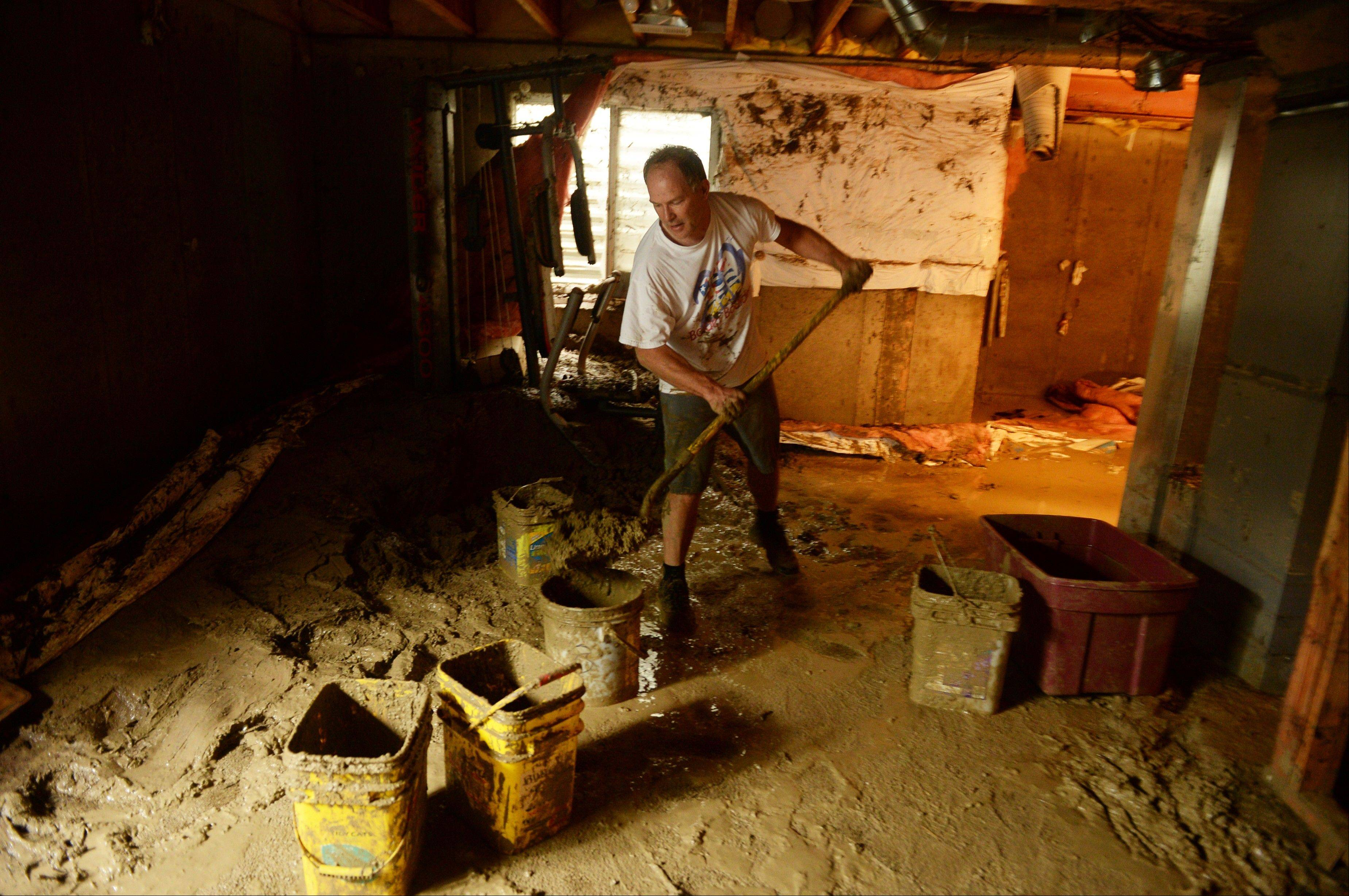 Mike Steinpach moves mud out from the basement of Stan McDonald's house damaged by flooding in Longmont, Colo., on Sunday.