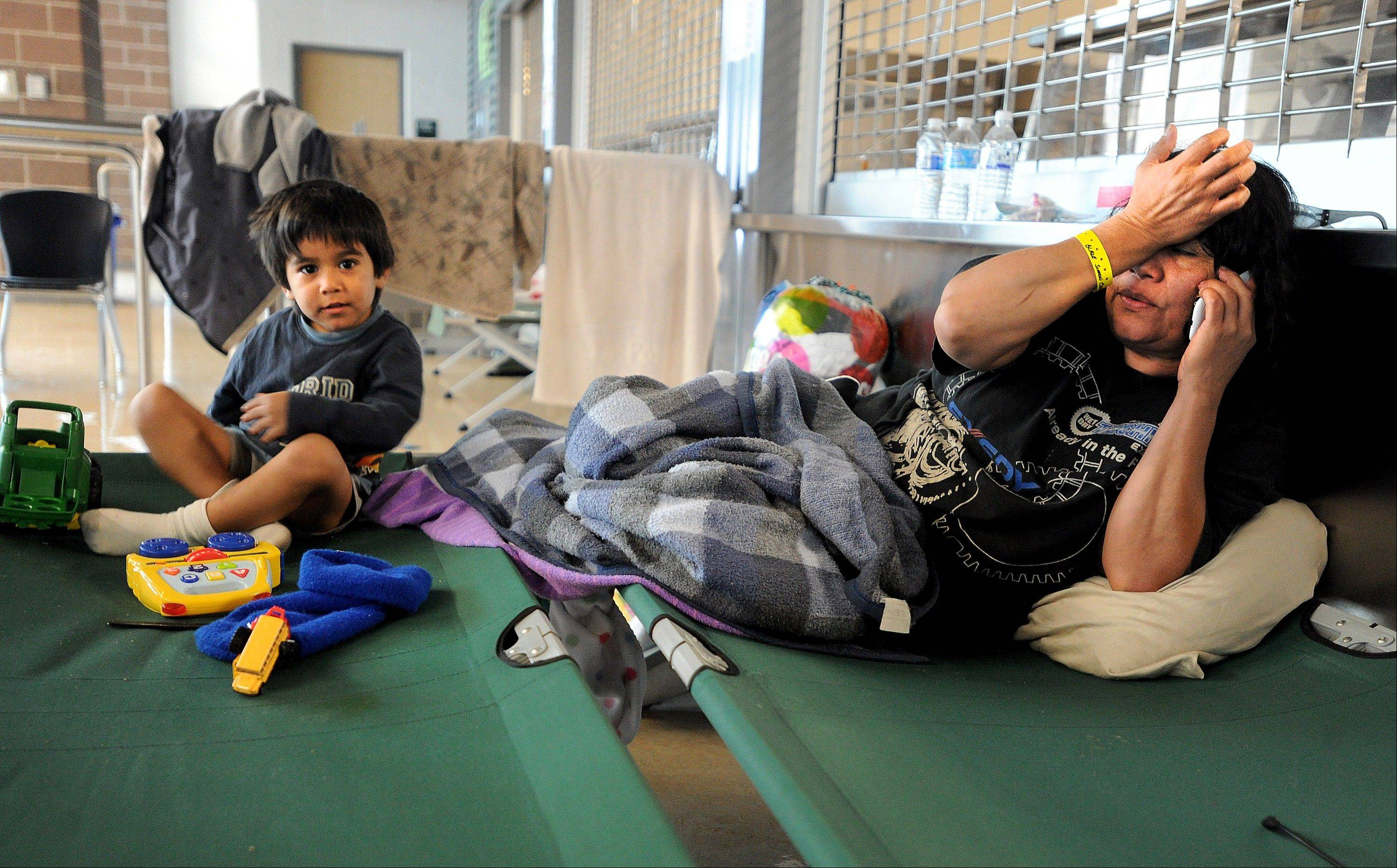 Carlos Duron, 3, and his mother, Vilma Maldonado, evacuees from Longmont, Colo., try to pass the time at Mead High School with the Red Cross on Sunday in Mead, Colo.
