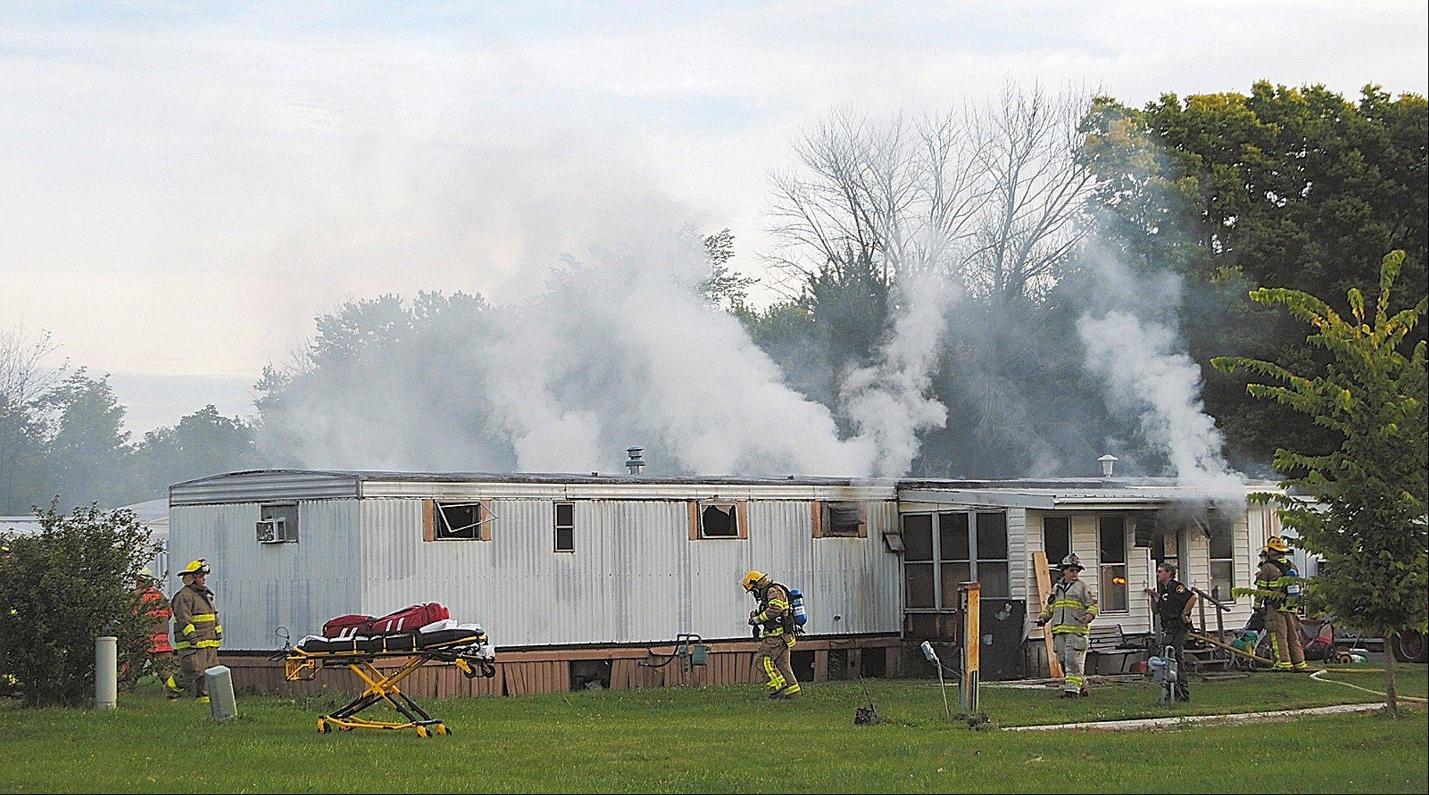 Firefighters extinguish a mobile home fire Sunday that killed a man and five children in Tiffin, Ohio, according to police.