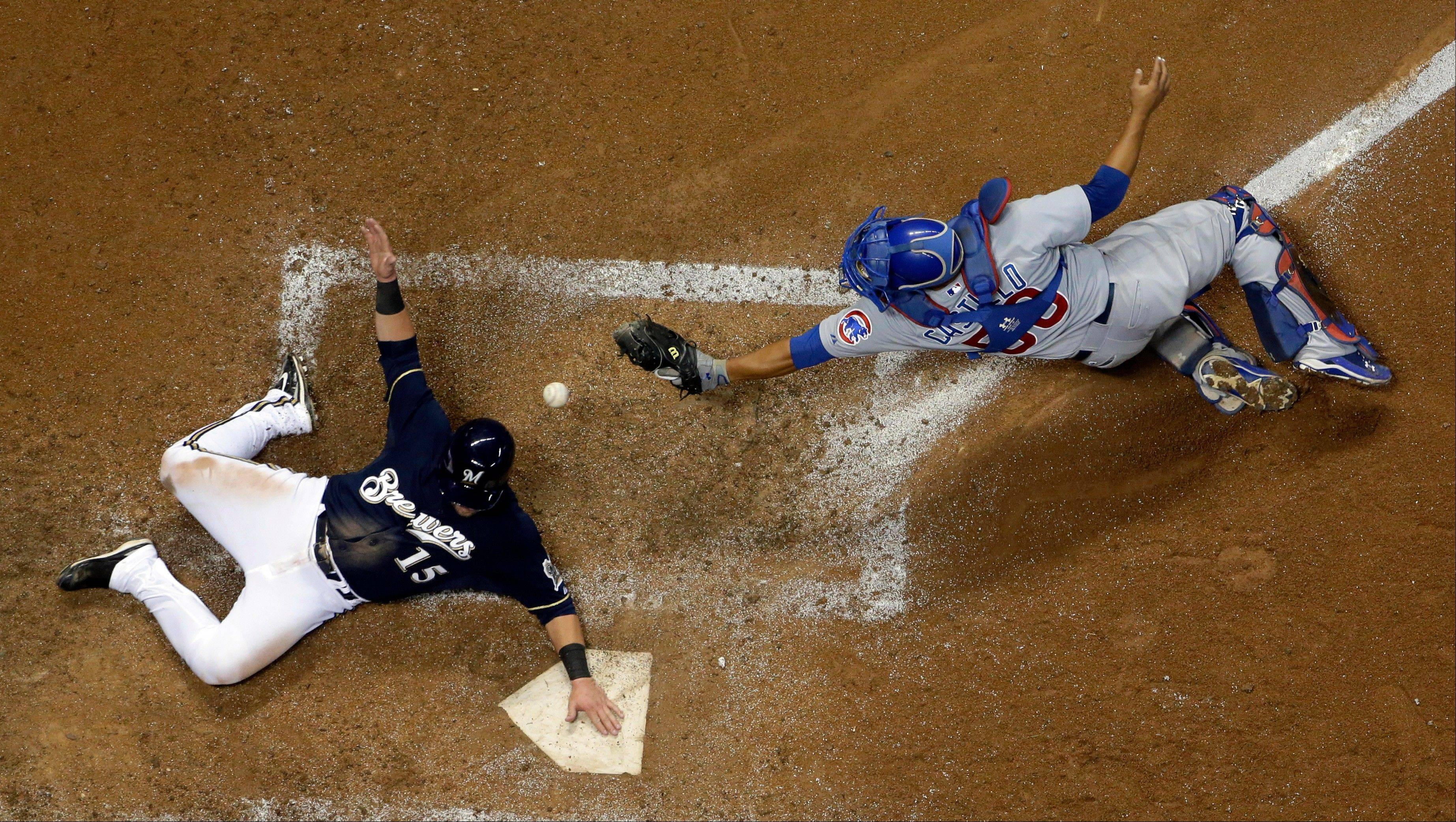 Milwaukee Brewers' Caleb Gindl slides safely past Chicago Cubs catcher Welington Castillo during the sixth inning of a baseball game, Monday, Sept. 16, 2013, in Milwaukee. Gindl scored from second on a hit by Yuniesky Betancourt.