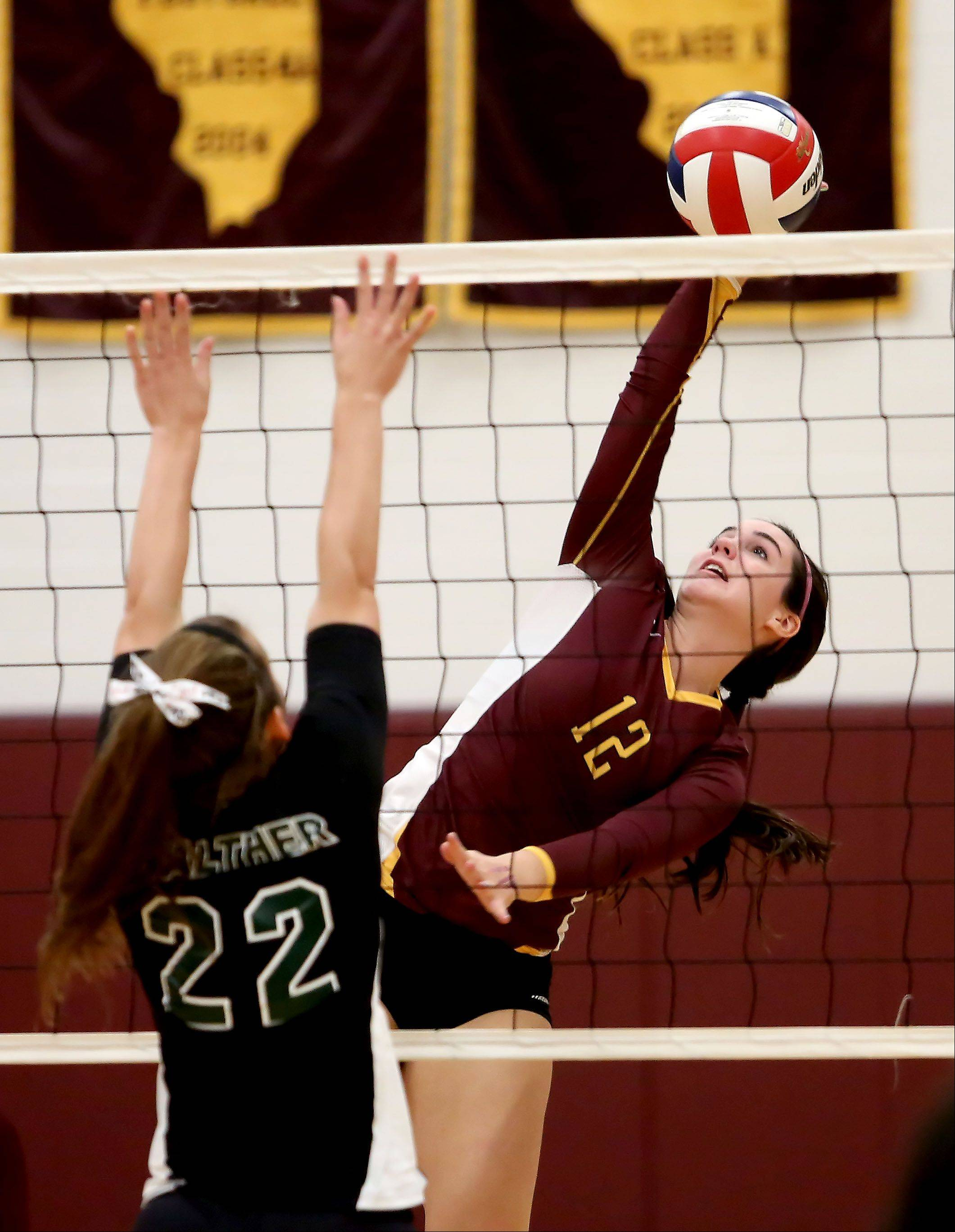 Kerry Desmond of Montini moves up to spike the ball past Miranda Heuser of Walther Christian, left, in girls volleyball action on Monday in Lombard.
