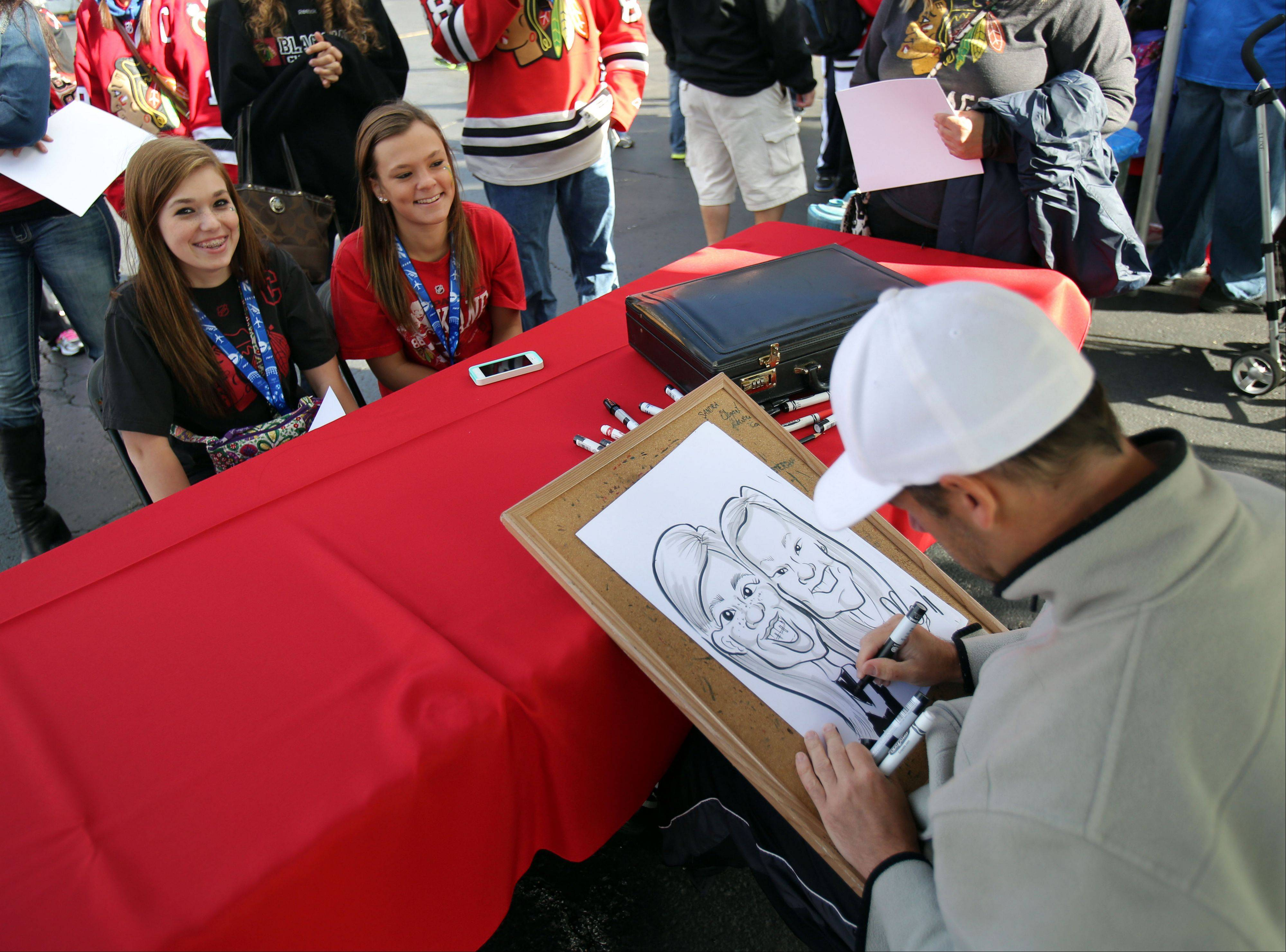Alyssa Bennardo, left, and Emily Koster, both 16 from Algonquin, get their portrait drawn by artist Scott Nychay.
