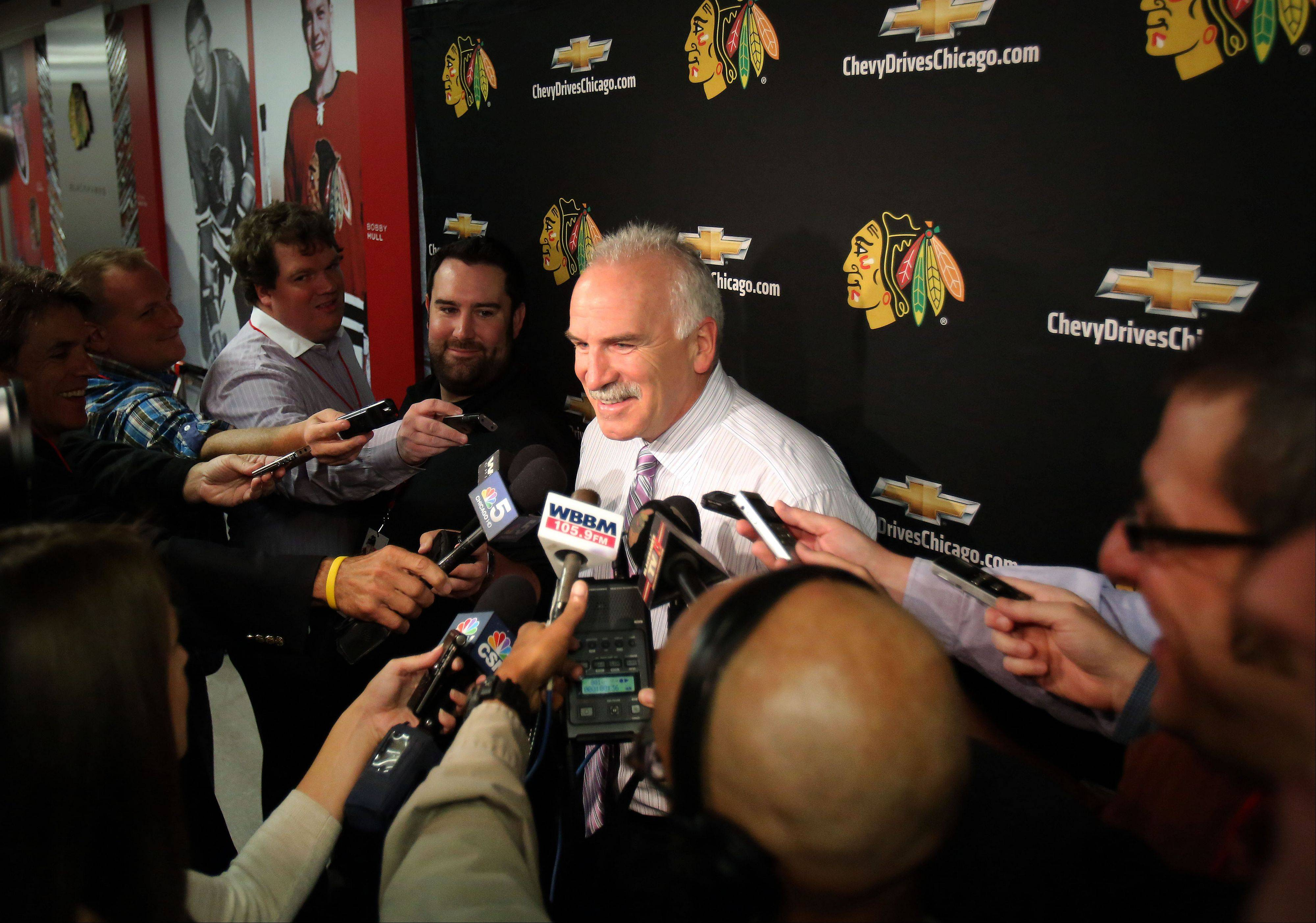 Blackhawks head coach Joel Quenneville answers questions from the media .