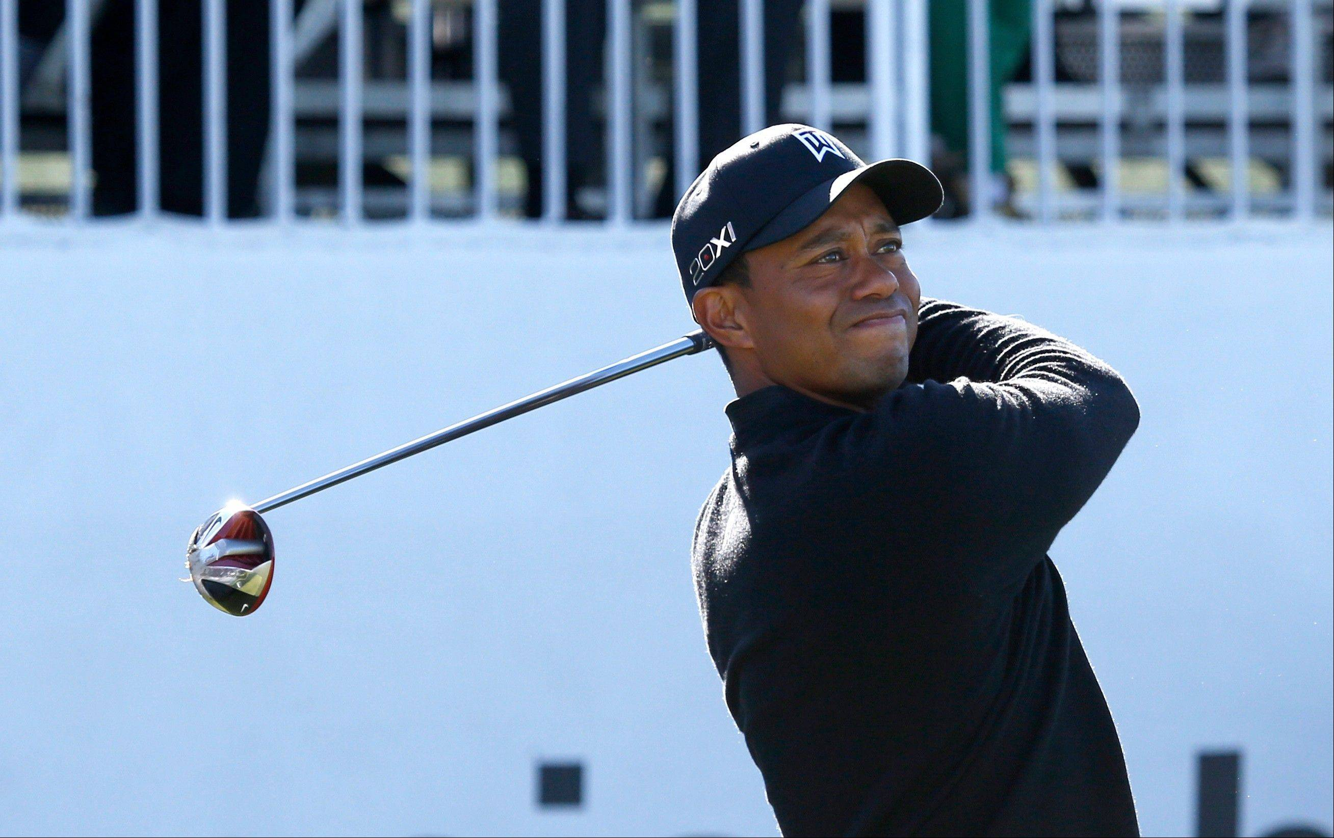 Tiger Woods watches his tee shot on the 1st hole.