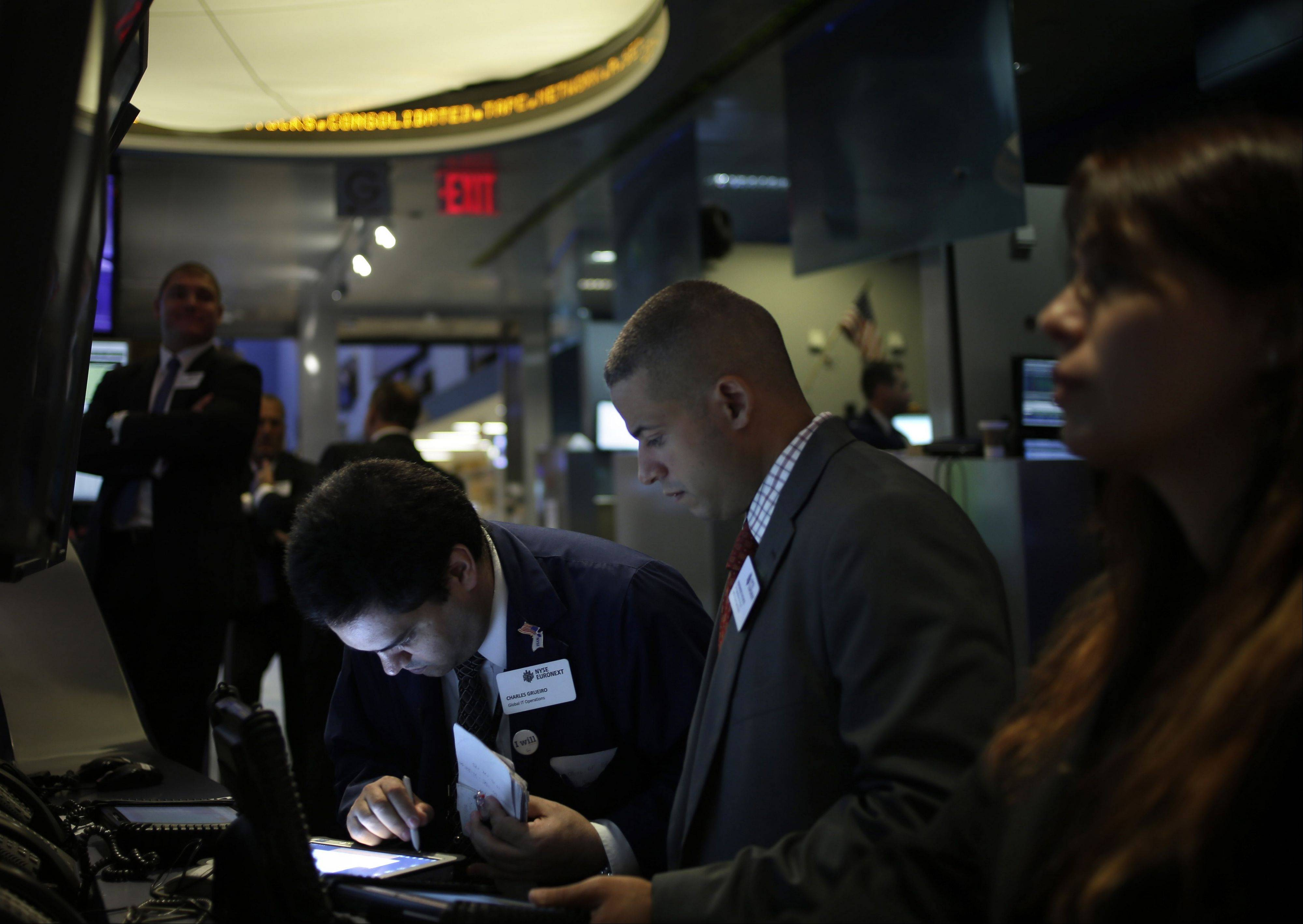 Associated Press Traders work on the floor at the New York Stock Exchange in New York. An Associated Press poll released Tuesday, of more than two dozen economists suggests that global growth will remain below full health into 2014.