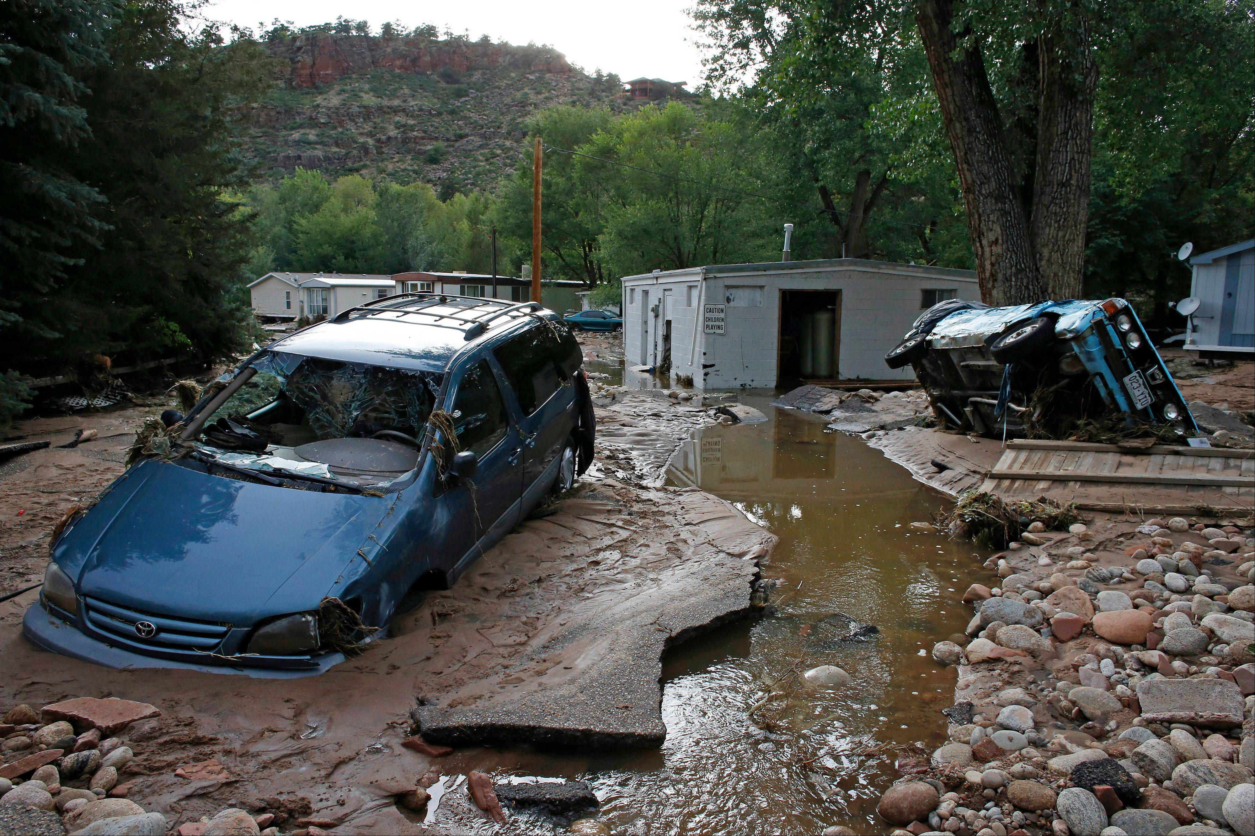 Cars lay mired in mud deposited by floods in Lyons, Colo.