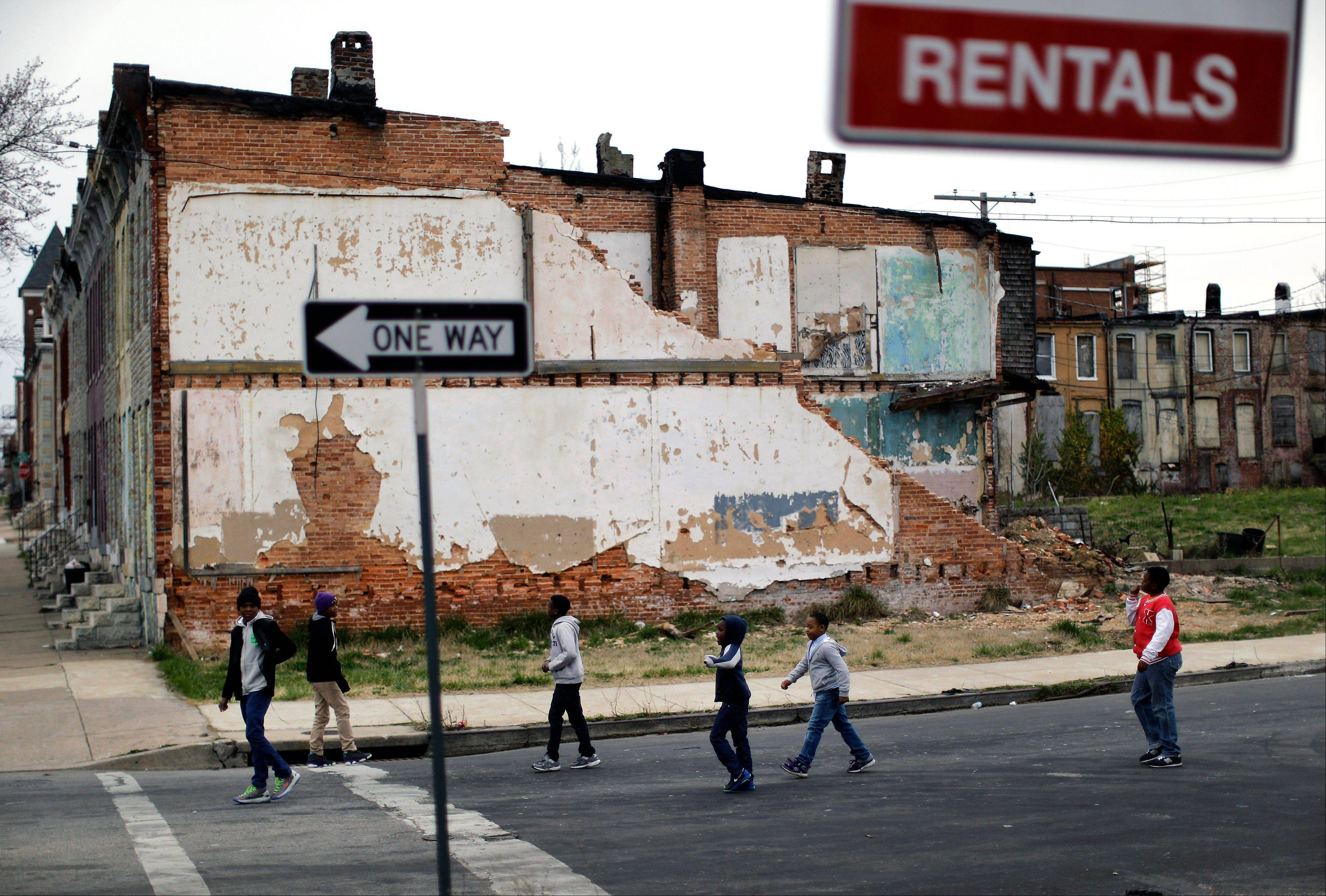 Boys walk past a partially collapsed row house in Baltimore. The nation�s poverty rate stood still at 15 percent in 2012, the sixth straight year it has failed to improve.