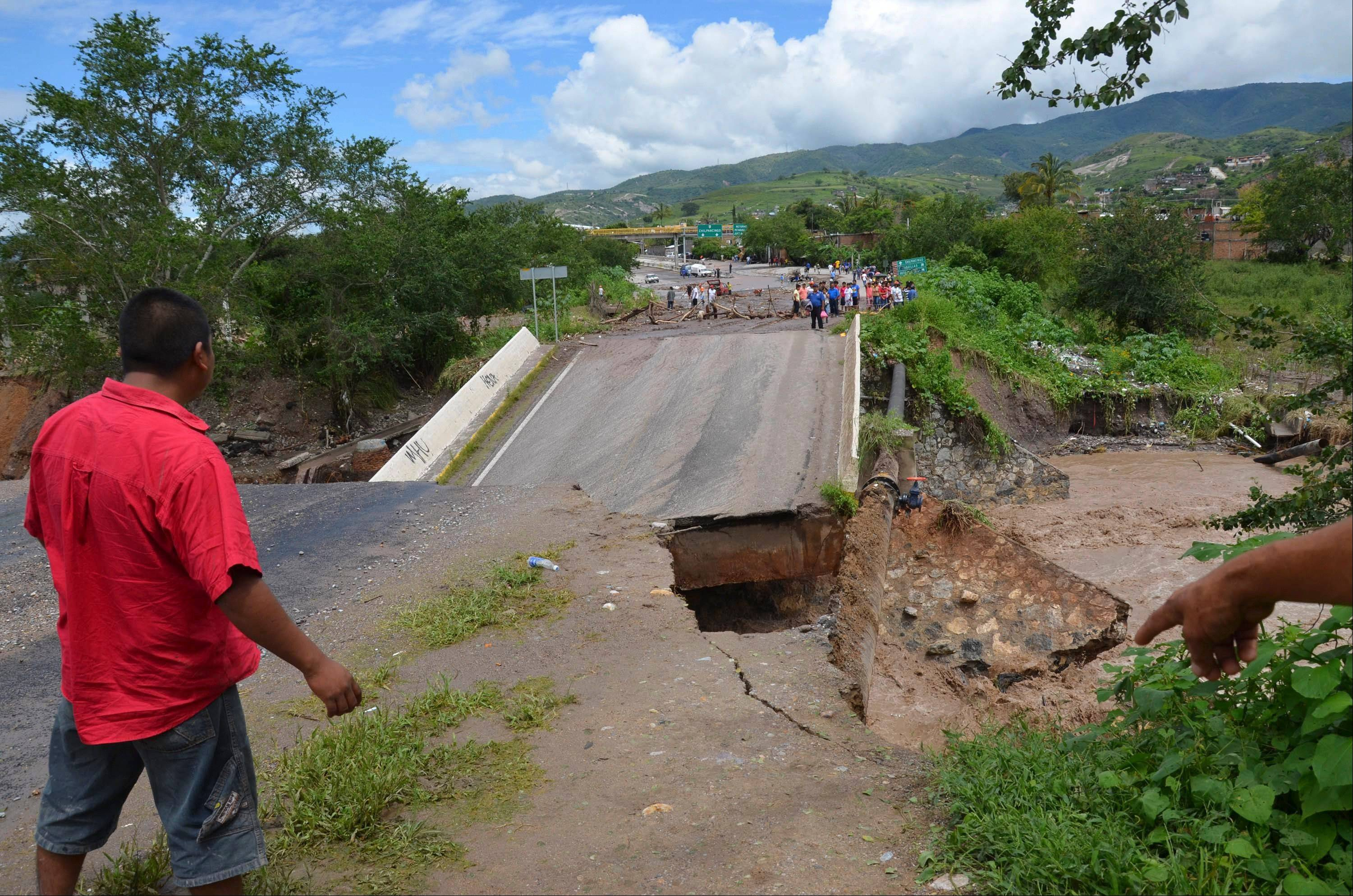 A man looks at a collapsed bridge over the Huacapa River near the town of Petaquillas, Mexico, Tuesday. Twin storms left scenes of havoc on both of Mexico's coasts on Tuesday, with tens of thousands of tourists stranded in resort city of Acapulco on the Pacific and heavy damage reported along the Gulf coast.