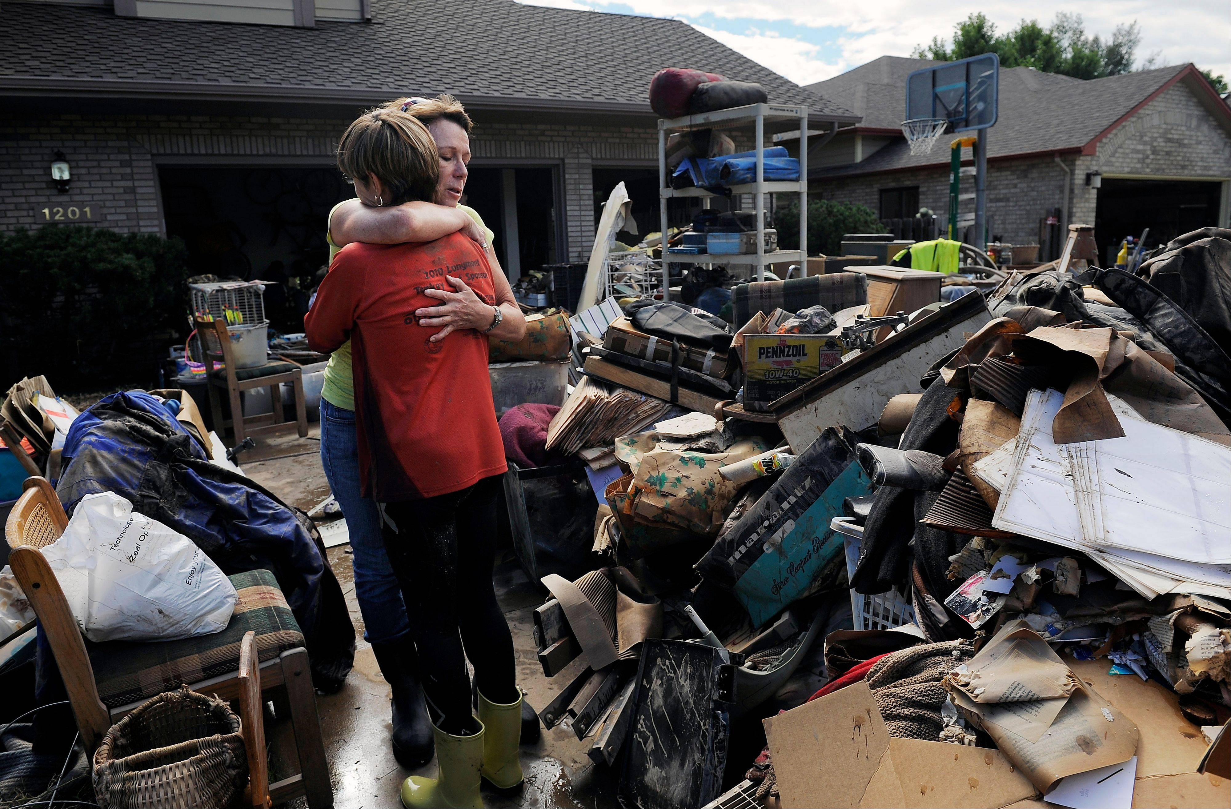 Homeowner Chris Ringdahl, left, is comforted by family friend Katherine MacIntosh, right, in front of her possessions as they cleanup from the floodwaters in Longmont, Colo., on Monday, Sept. 16, 2013. Floodwaters have affected a 4,500 square-mile section of the state inundating entire neighborhoods and destroying bridges and roads.