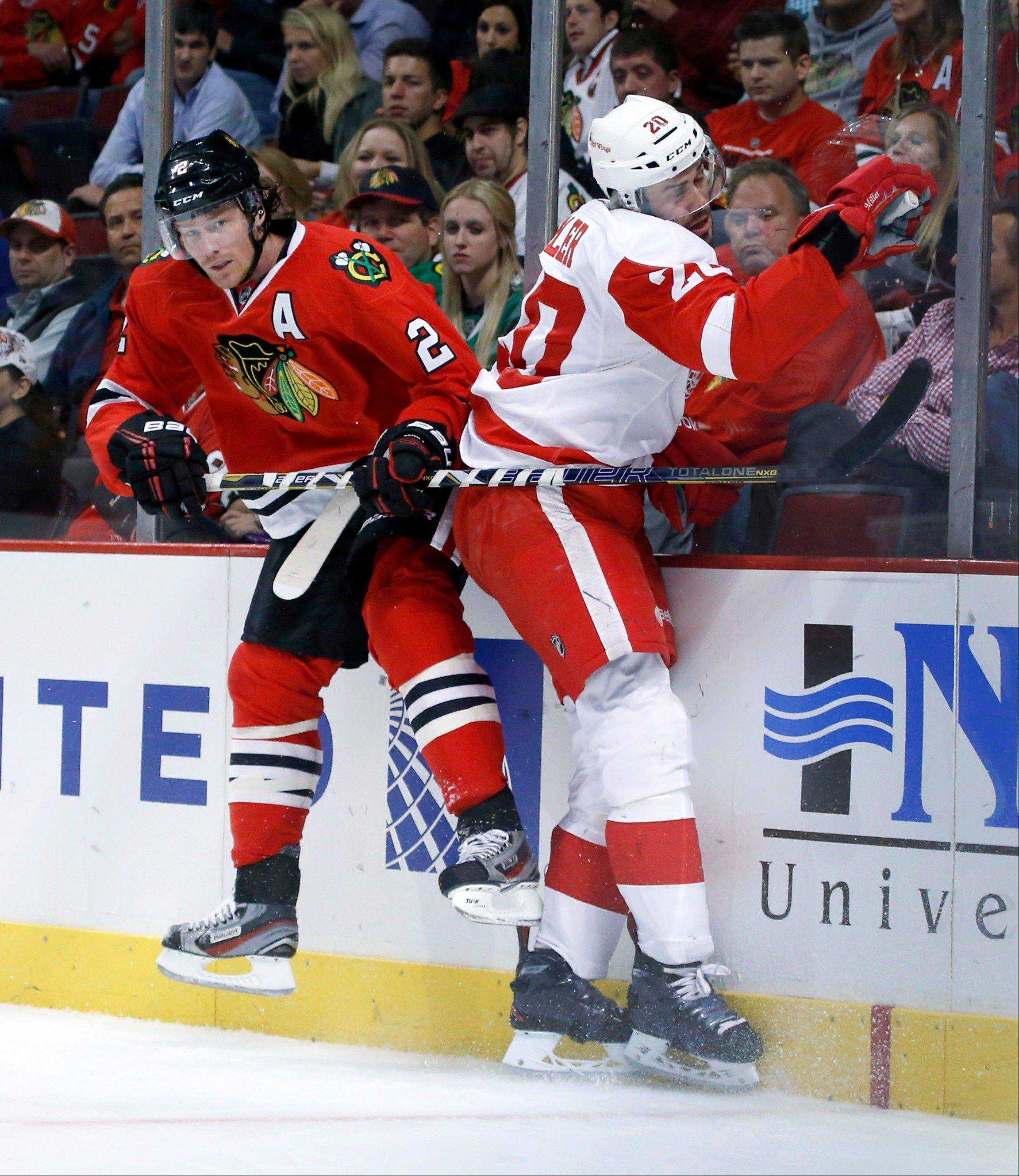 Blackhawks defenseman Duncan Keith checks Detroit Red Wings left wing Drew Miller into the boards during the first period Tuesday night at the United Center.