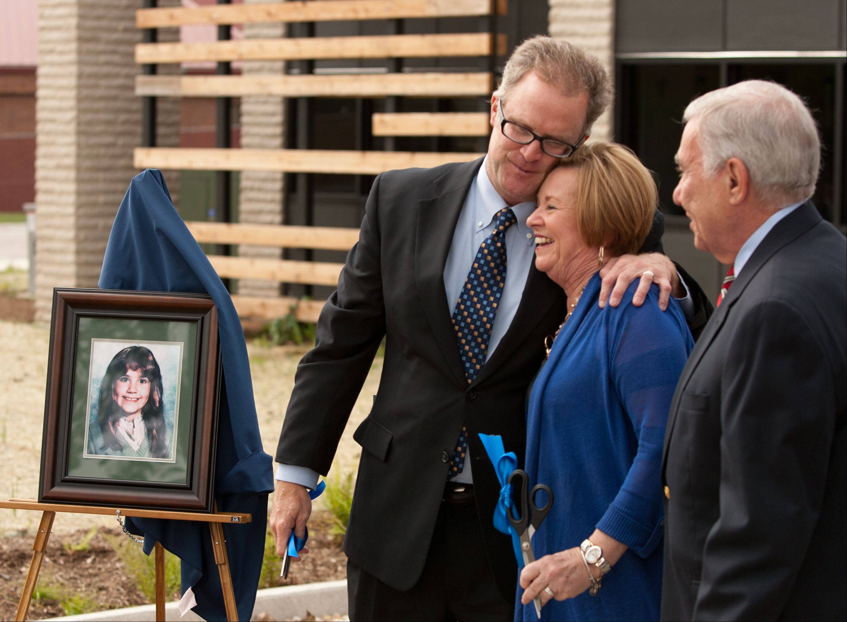 DuPage County Board Chairman Dan Cronin embraces Pat Nicarico during the dedication of the new Jeanine Nicarico Children's Advocacy Center in Wheaton. Tom Nicarico is at right.