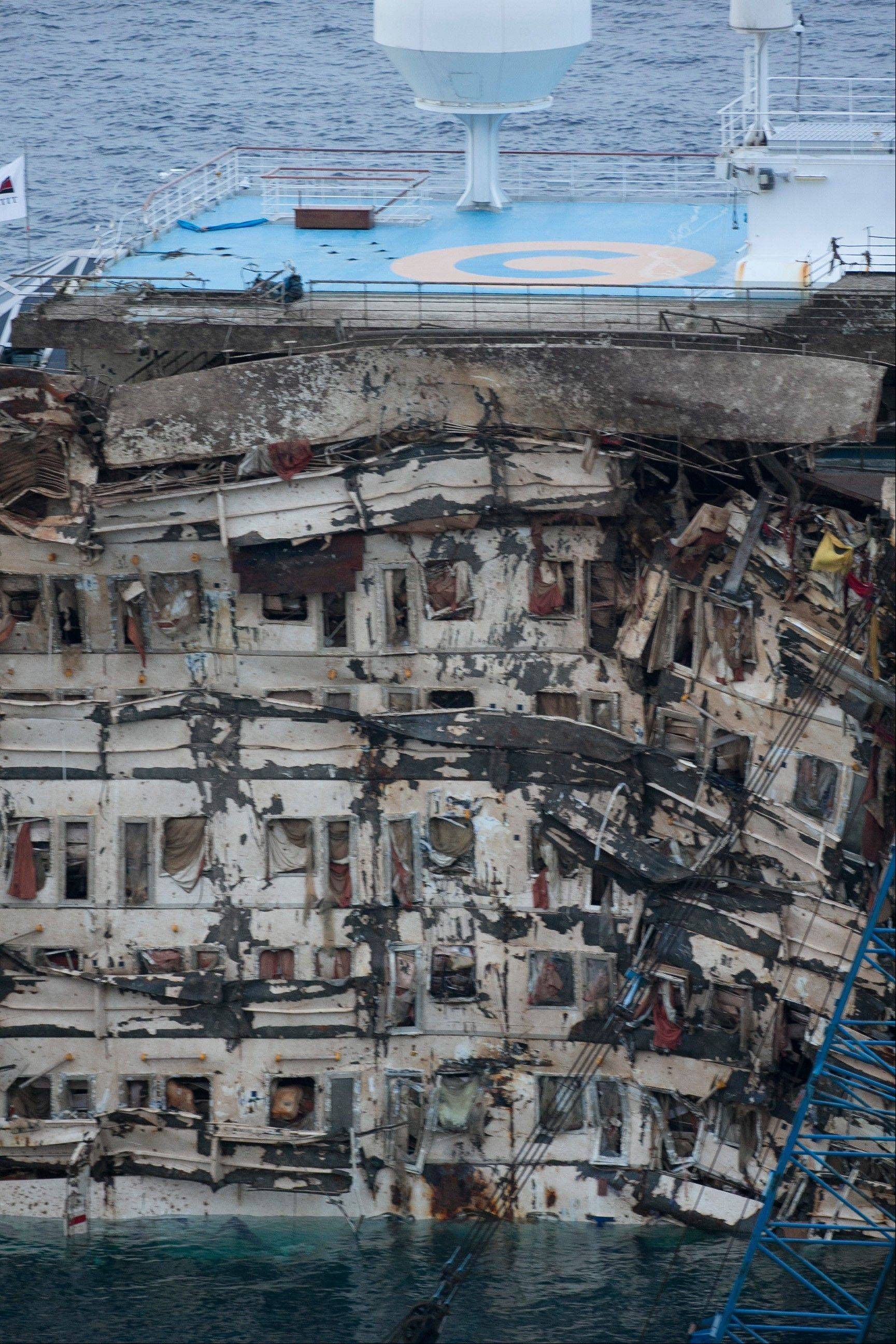 "A detail of the right side of the Costa Concordia is seen after it was lifted upright on the Tuscan Island of Giglio, Italy, early Tuesday morning, Sept. 17, 2013. The crippled cruise ship was pulled completely upright early Tuesday after a complicated, 19-hour operation to wrench it from its side where it capsized last year off Tuscany, with officials declaring it a ""perfect"" end to a daring and unprecedented engineering feat."
