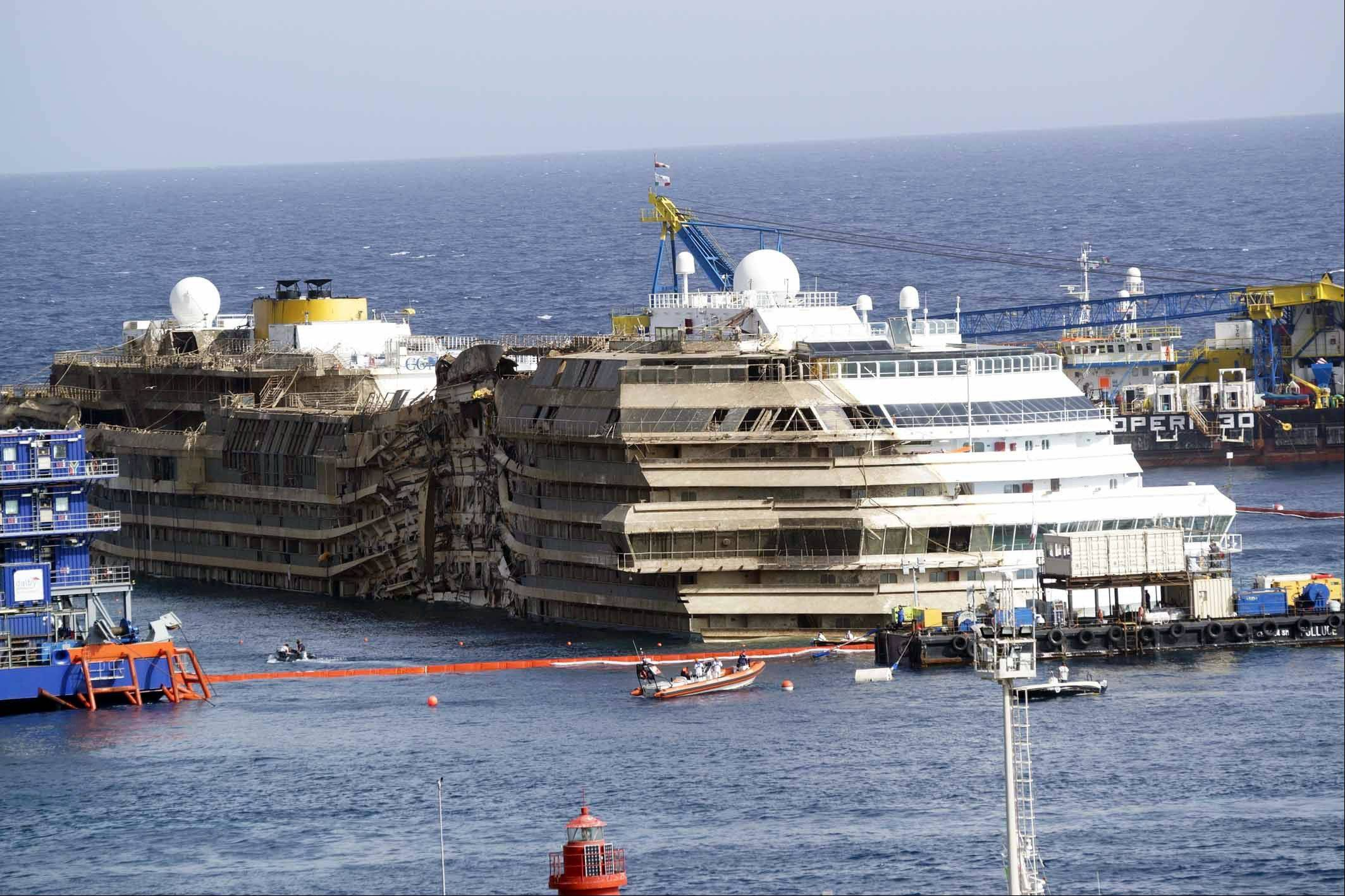 The Costa Concordia ship is seen after it was lifted upright, on the Tuscan Island of Giglio, Italy, Tuesday morning, Sept. 17, 2013. Engineers declared success on Tuesday as the Costa Concordia cruise ship was pulled completely upright during a complicated, 19-hour operation to wrench it from its side where it capsized last year off Tuscany, an unprecedented feat that sets the stage for it to be towed away next year.