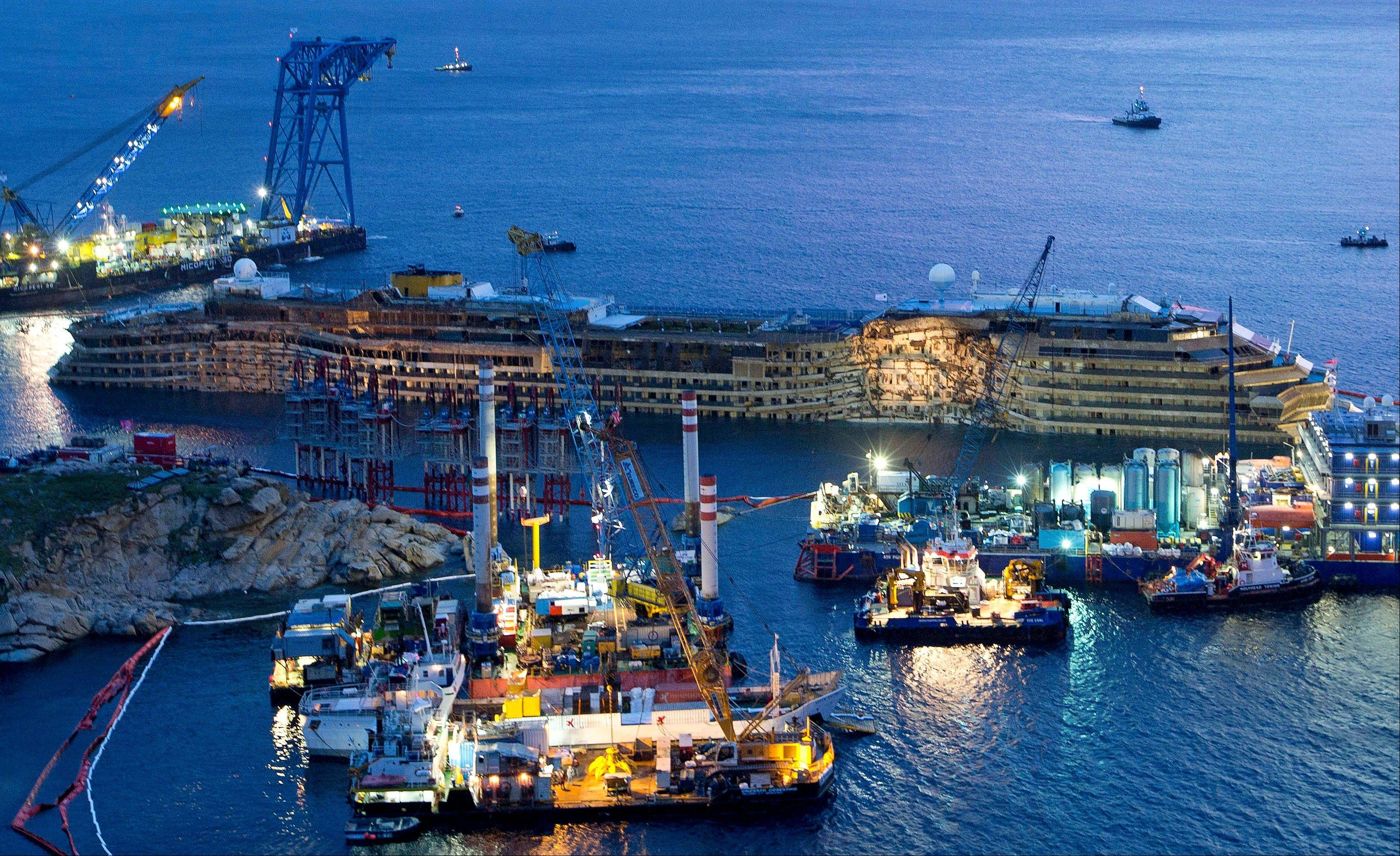 "The Costa Concordia is seen after it was lifted upright, on the Tuscan Island of Giglio, Italy, early Tuesday morning, Sept. 17, 2013. The crippled cruise ship was pulled completely upright early Tuesday after a complicated, 19-hour operation to wrench it from its side where it capsized last year off Tuscany, with officials declaring it a ""perfect"" end to a daring and unprecedented engineering feat."