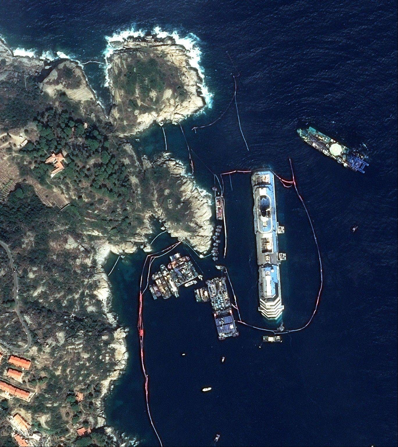 This photo provided by Astrium shows the upright Costa Concordia off Giglio Island, Italy, Tuesday, Sept.17, 2013 . Engineers declared success on Tuesday, Sept.17, 2013 as the Costa Concordia cruise ship was pulled completely upright during an unprecedented, 19-hour operation to wrench it from its side where it capsized last year off Tuscany.