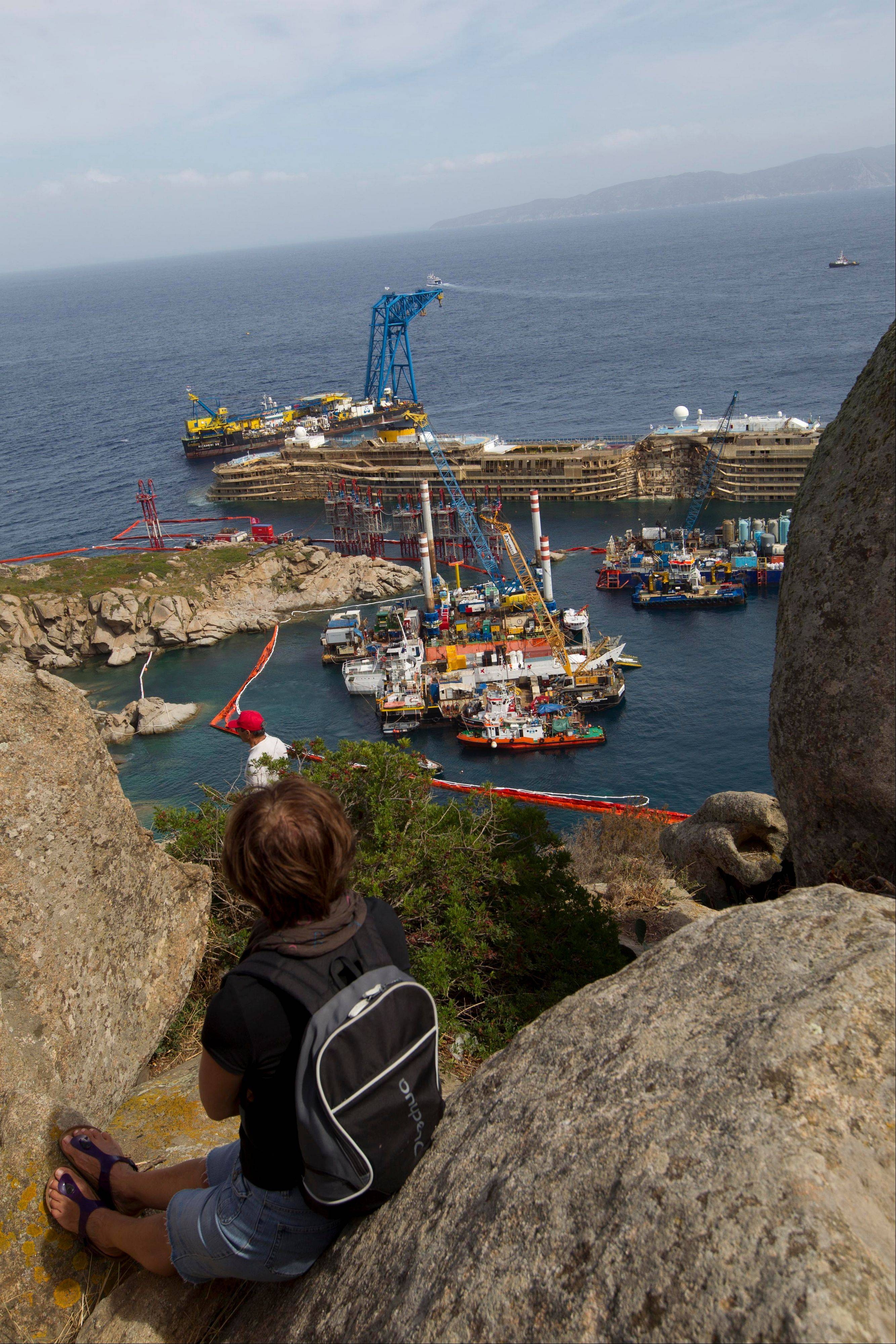 A woman looks at the Costa Concordia is seen after it was lifted upright, on the Tuscan Island of Giglio, Italy, Tuesday, Sept. 17, 2013. Engineers declared success on Tuesday as the Costa Concordia cruise ship was pulled completely upright during a complicated, 19-hour operation to wrench it from its side where it capsized last year off Tuscany, an unprecedented feat that sets the stage for it to be towed away next year.