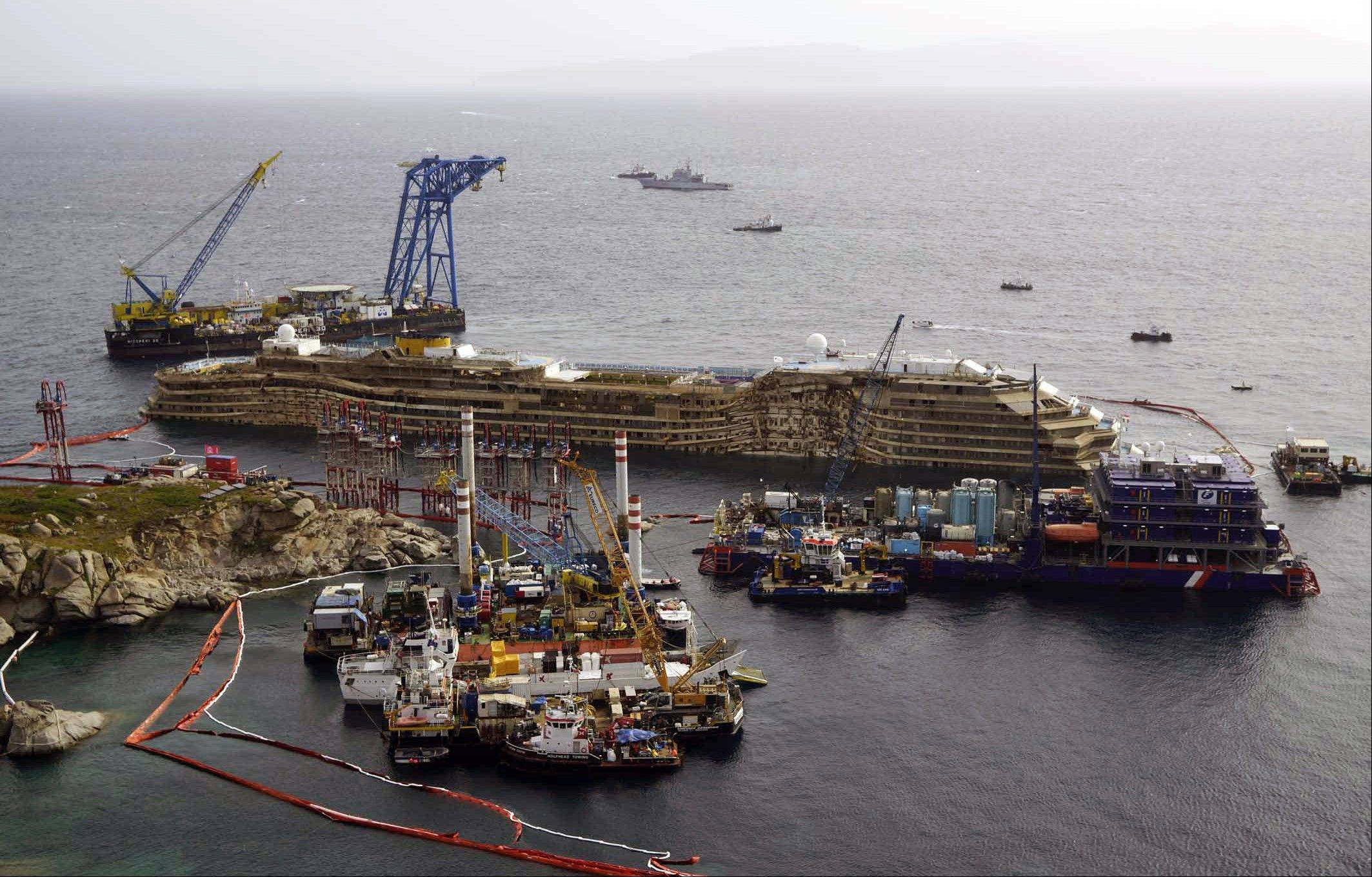 "The Costa Concordia ship is seen after it was lifted upright, on the Tuscan Island of Giglio, Italy, Tuesday morning, Sept. 17, 2013. The crippled cruise ship was pulled completely upright early Tuesday after a complicated, 19-hour operation to wrench it from its side where it capsized last year off Tuscany, with officials declaring it a ""perfect"" end to a daring and unprecedented engineering feat."