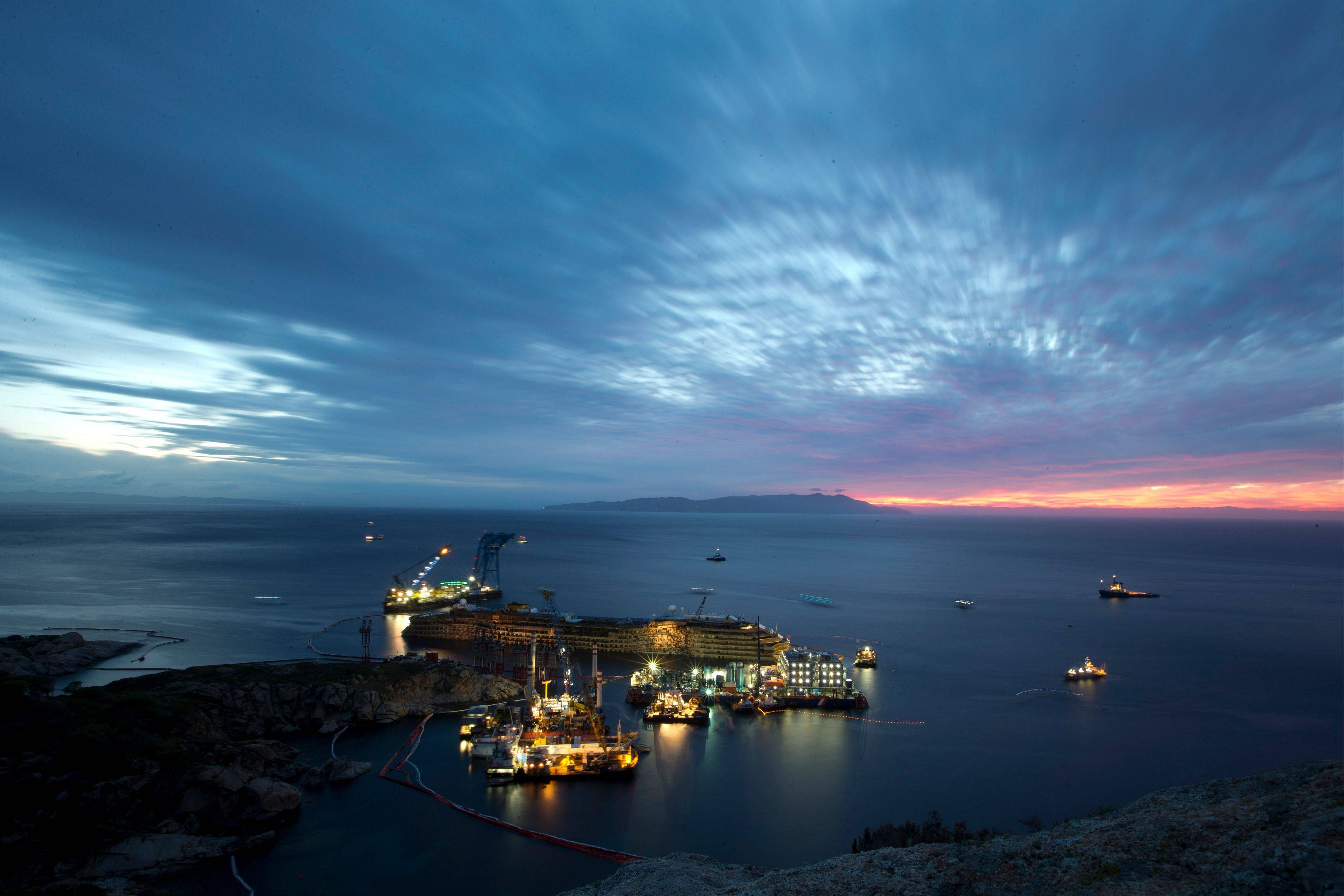 "The Costa Concordia is seen after it was lifted upright on the Tuscan Island of Giglio, Italy, early Tuesday morning, Sept. 17, 2013. The crippled cruise ship was pulled completely upright early Tuesday after a complicated, 19-hour operation to wrench it from its side where it capsized last year off Tuscany, with officials declaring it a ""perfect"" end to a daring and unprecedented engineering feat."