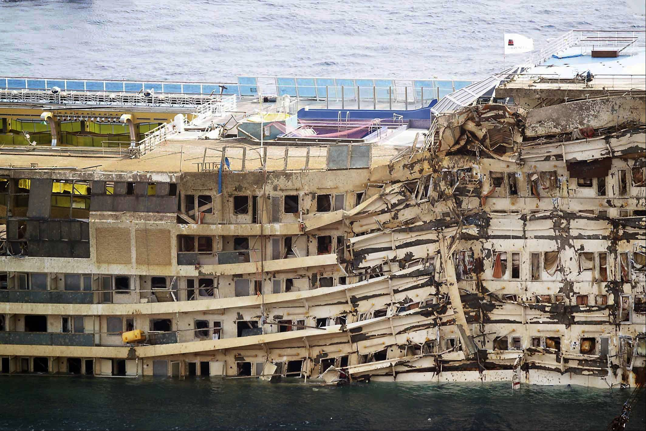 "The Costa Concordia is seen after it was lifted upright, on the Tuscan Island of Giglio, Italy, Tuesday, Sept. 17, 2013. The crippled cruise ship was pulled completely upright early Tuesday after a complicated, 19-hour operation to wrench it from its side where it capsized last year off Tuscany, with officials declaring it a ""perfect"" end to a daring and unprecedented engineering feat."