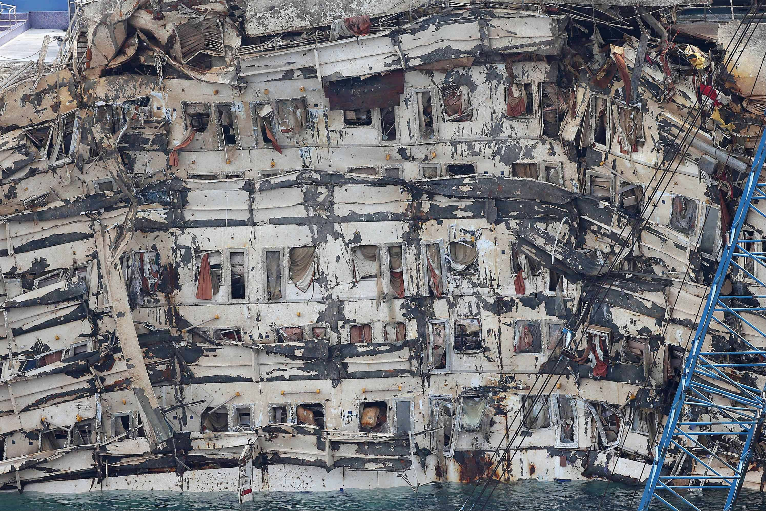 "A detail of the previously submerged side of the Costa Concordia is seen after it was lifted upright, on the Tuscan Island of Giglio, Italy, Tuesday, Sept. 17, 2013. The crippled cruise ship was pulled completely upright early Tuesday after a complicated, 19-hour operation to wrench it from its side where it capsized last year off Tuscany, with officials declaring it a ""perfect"" end to a daring and unprecedented engineering feat."