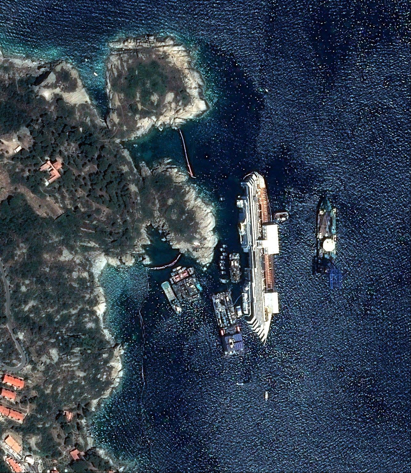 This photo provided by Astrium Tuesday, Sept.17, 2013 shows the capsized Costa Concordia on July 12, 2013. Engineers declared success on Tuesday, Sept.17, 2013 as the Costa Concordia cruise ship was pulled completely upright during an unprecedented 19-hour operation to wrench it from its side where it capsized last year off Tuscany.