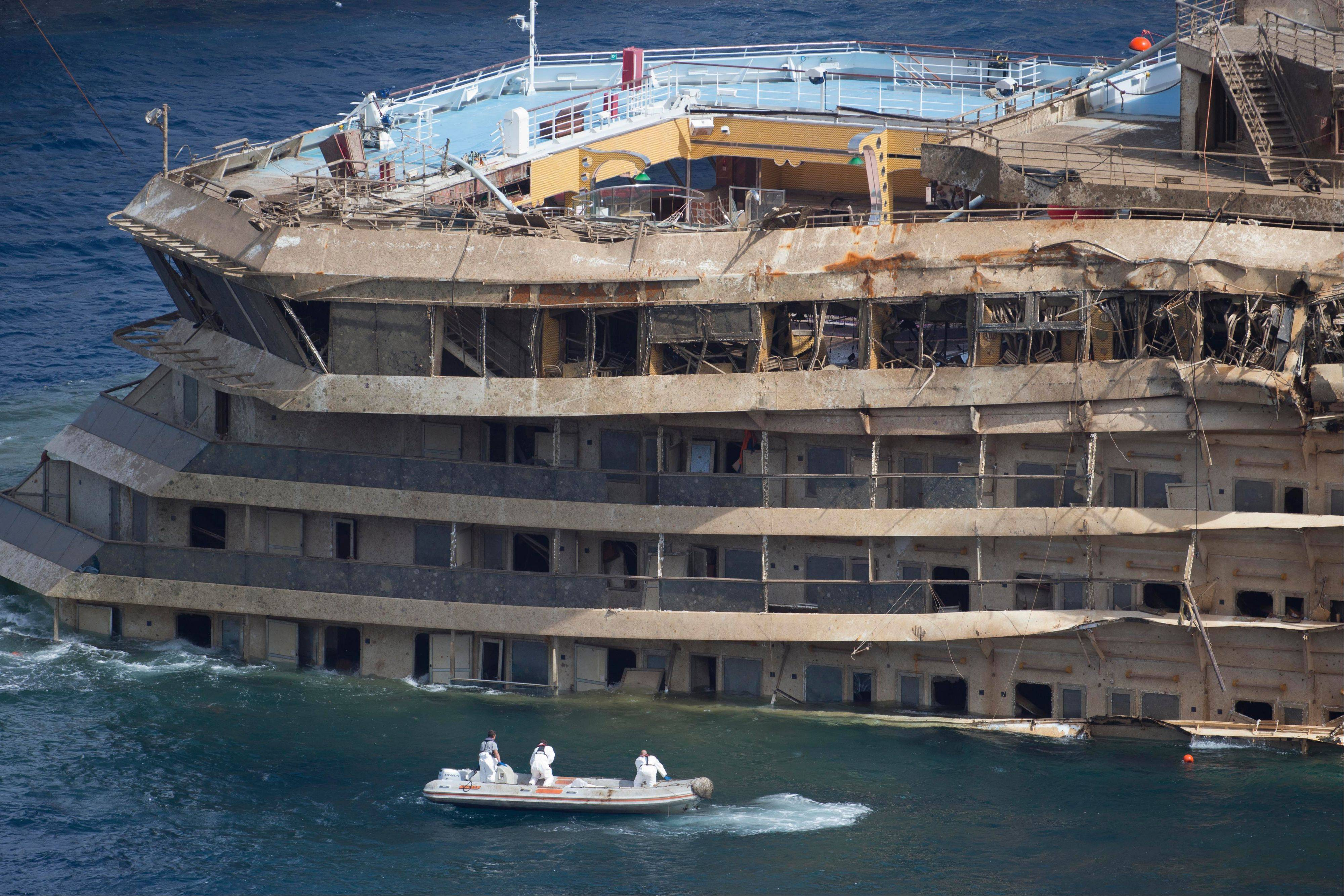 Workers on a boat sail past the Costa Concordia ship after it was lifted upright, on the Tuscan Island of Giglio, Italy, Tuesday, Sept. 17, 2013. Engineers declared success on Tuesday as the Costa Concordia cruise ship was pulled completely upright during a complicated, 19-hour operation to wrench it from its side where it capsized last year off Tuscany, an unprecedented feat that sets the stage for it to be towed away next year.