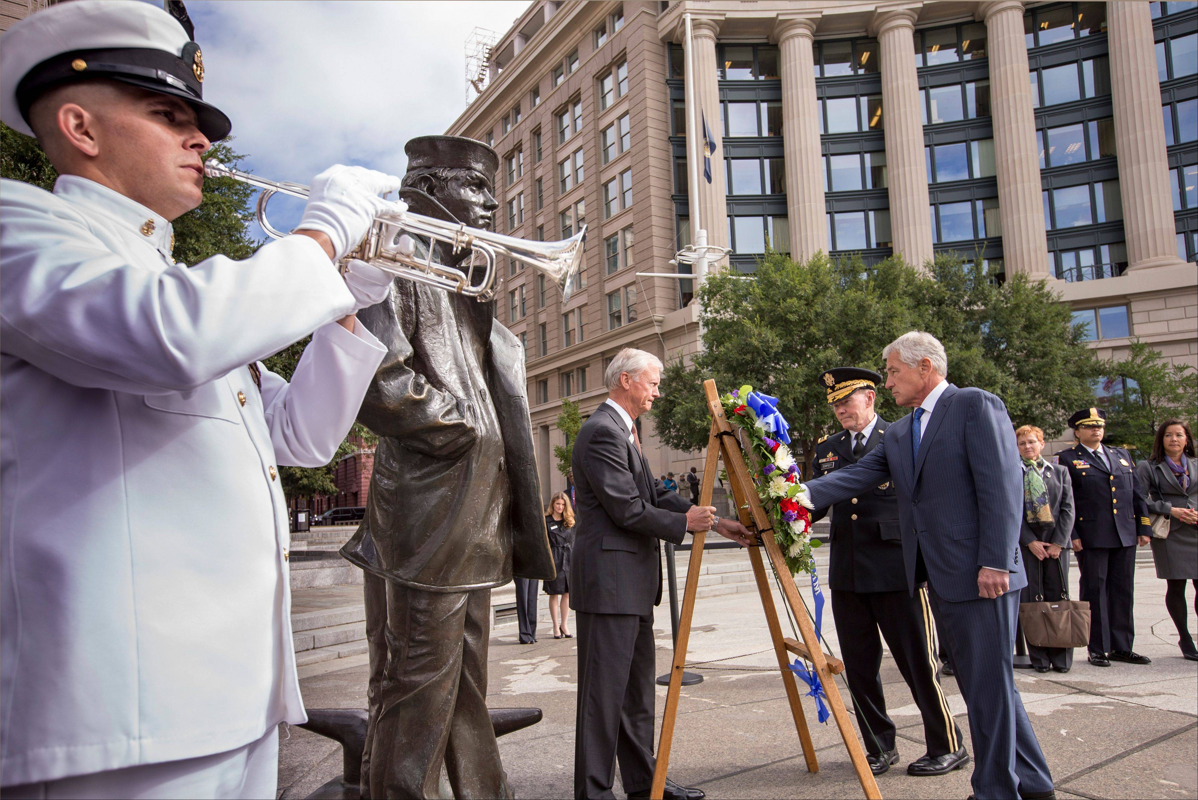 Defense Secretary Chuck Hagel, right, and Joint Chiefs Chairman Gen. Martin Dempsey, second from right, present a wreath at the Navy Memorial in Washington to remember the victims of Monday's deadly shooting at the Washington Navy Yard, Tuesday, Sept. 17, 2013.