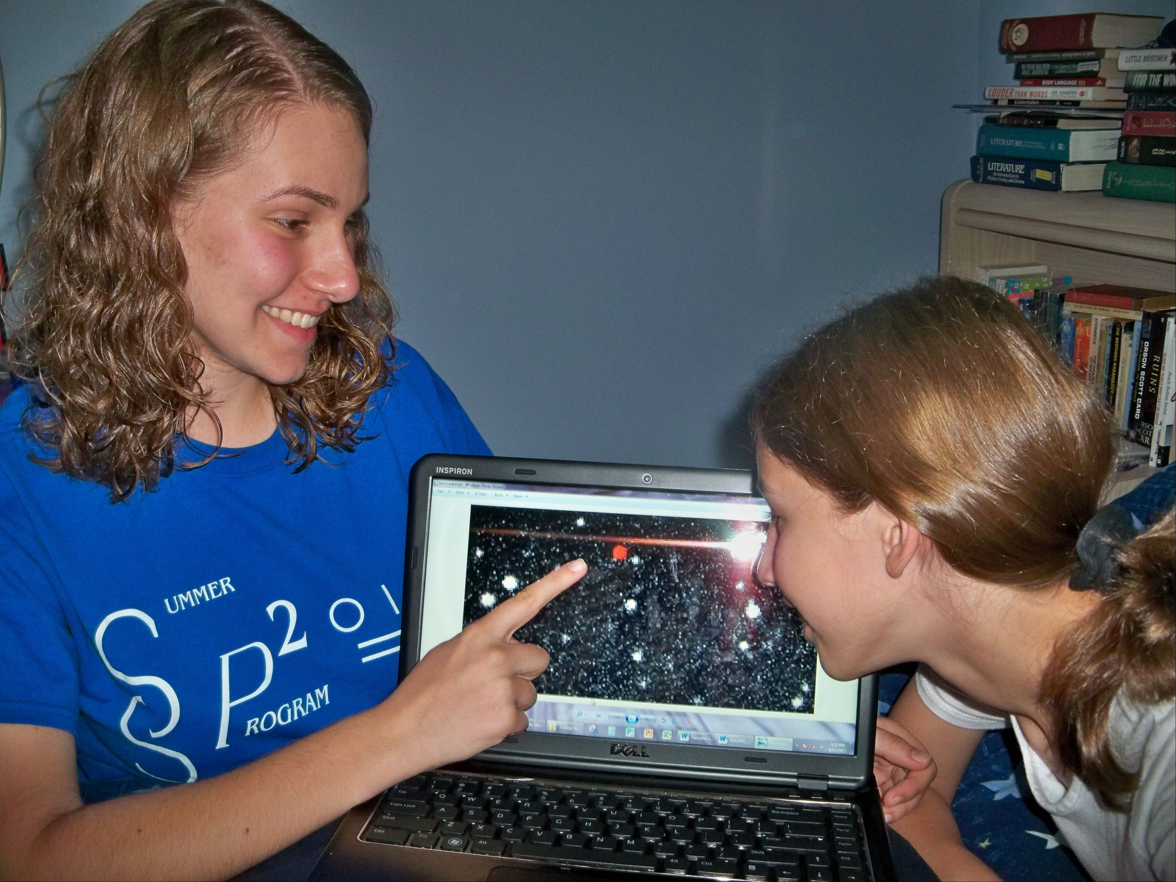 Naperville student Kimberly Dauber, left, points out the asteroid she observed to her sister, Angie.