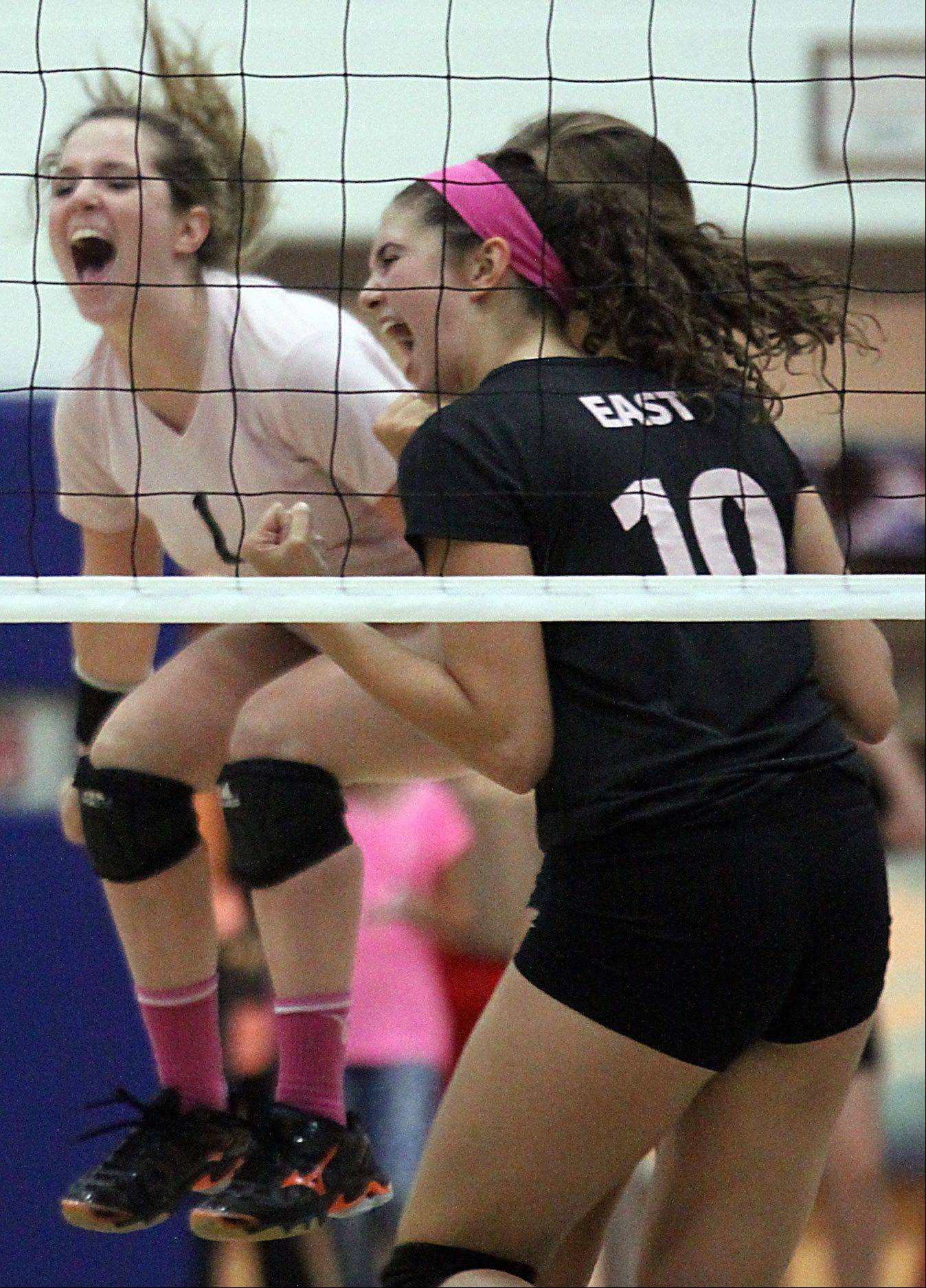 St. Charles East's Anne Hughes, left, and Mikaela Mosquera celebrate a point during a varsity volleyball game at St. Charles North on Tuesday evening.