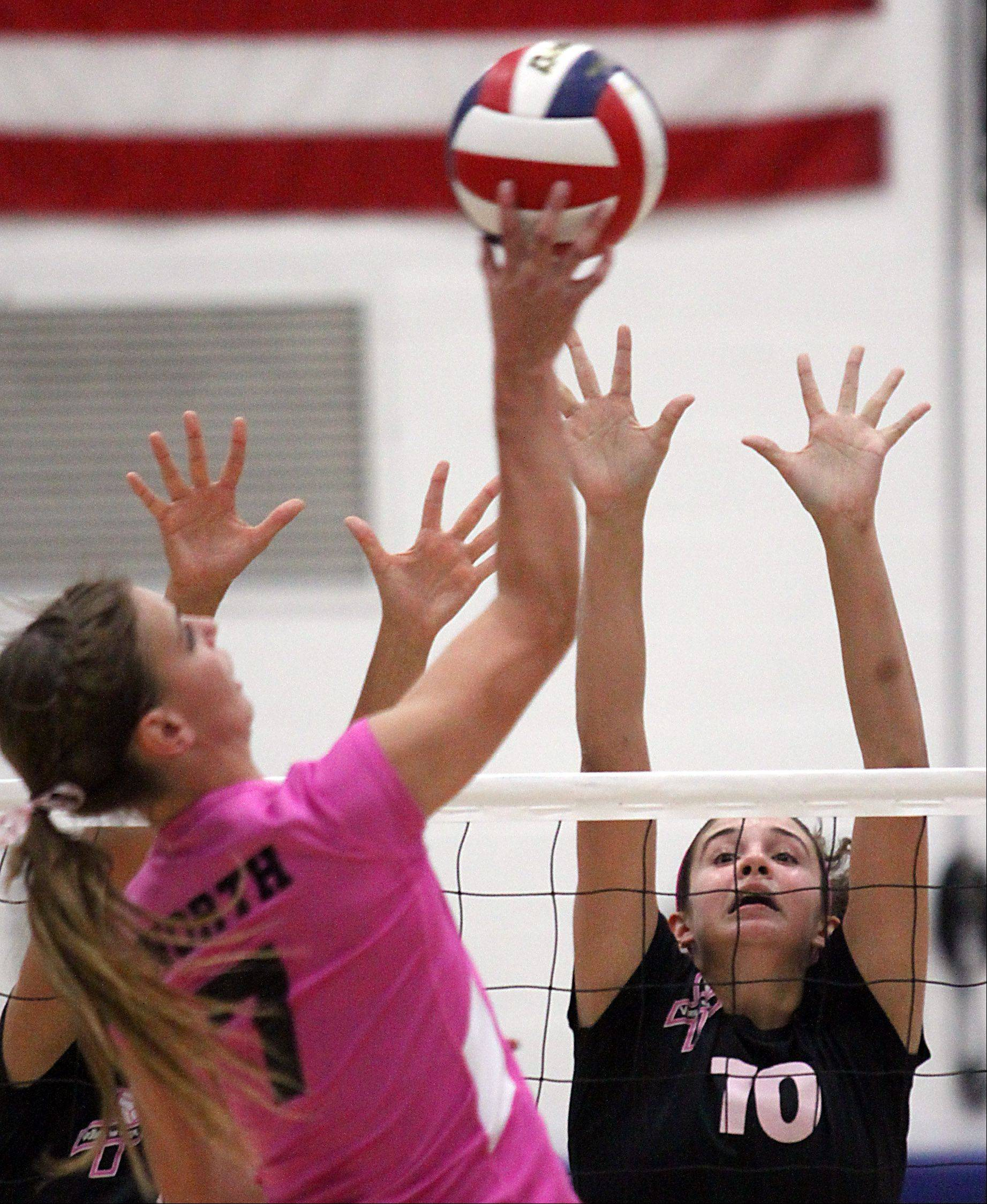 St. Charles North's Taylor Krage, left, tries to get the ball past St. Charles East's Mikaela Mosquera during a varsity volleyball game at St. Charles North on Tuesday evening.