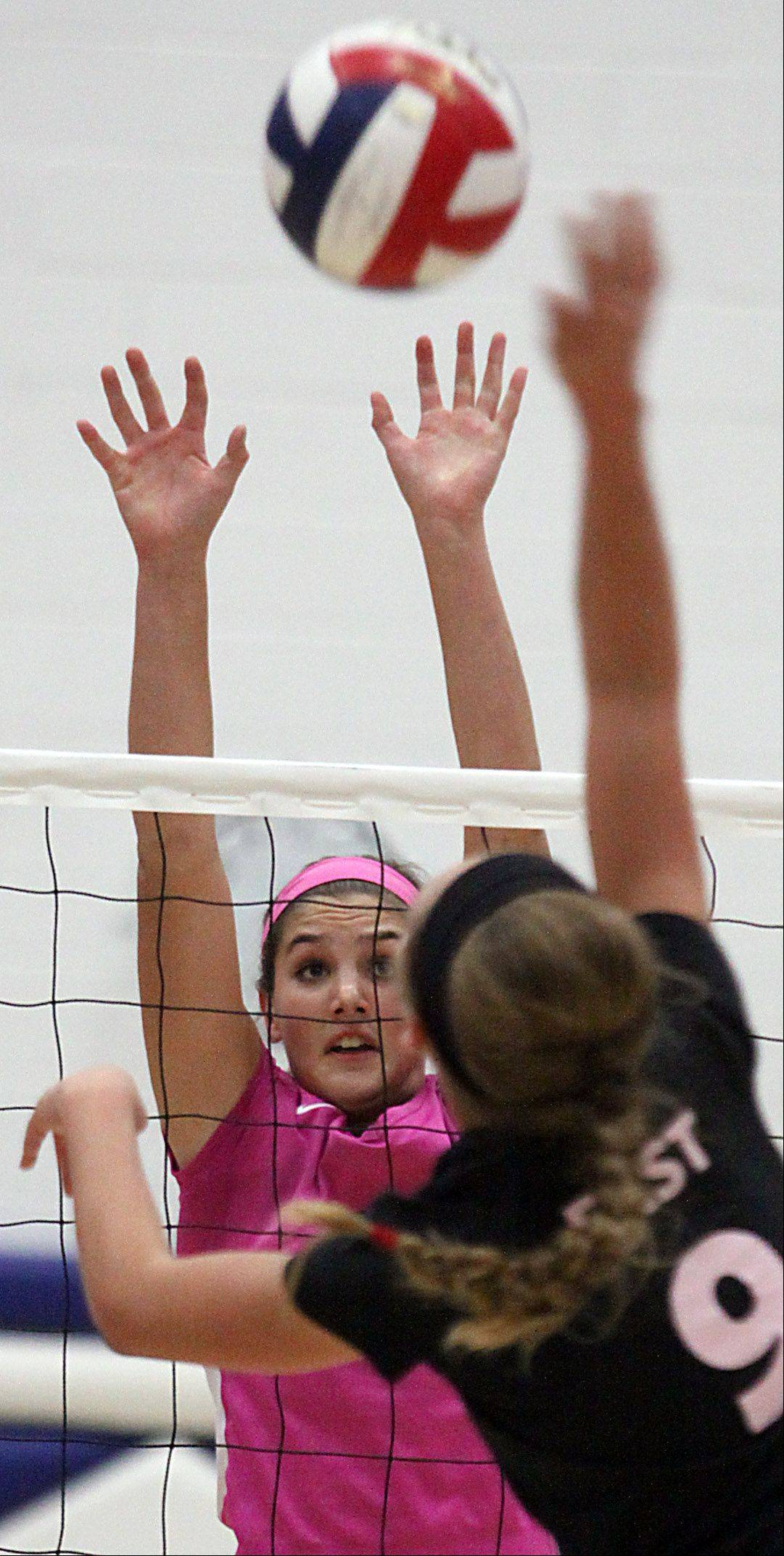 St. Charles North's Daley Krage, left, goes up to block St. Charles East's Megan Schildmeyer during a varsity volleyball game at St. Charles North on Tuesday evening.
