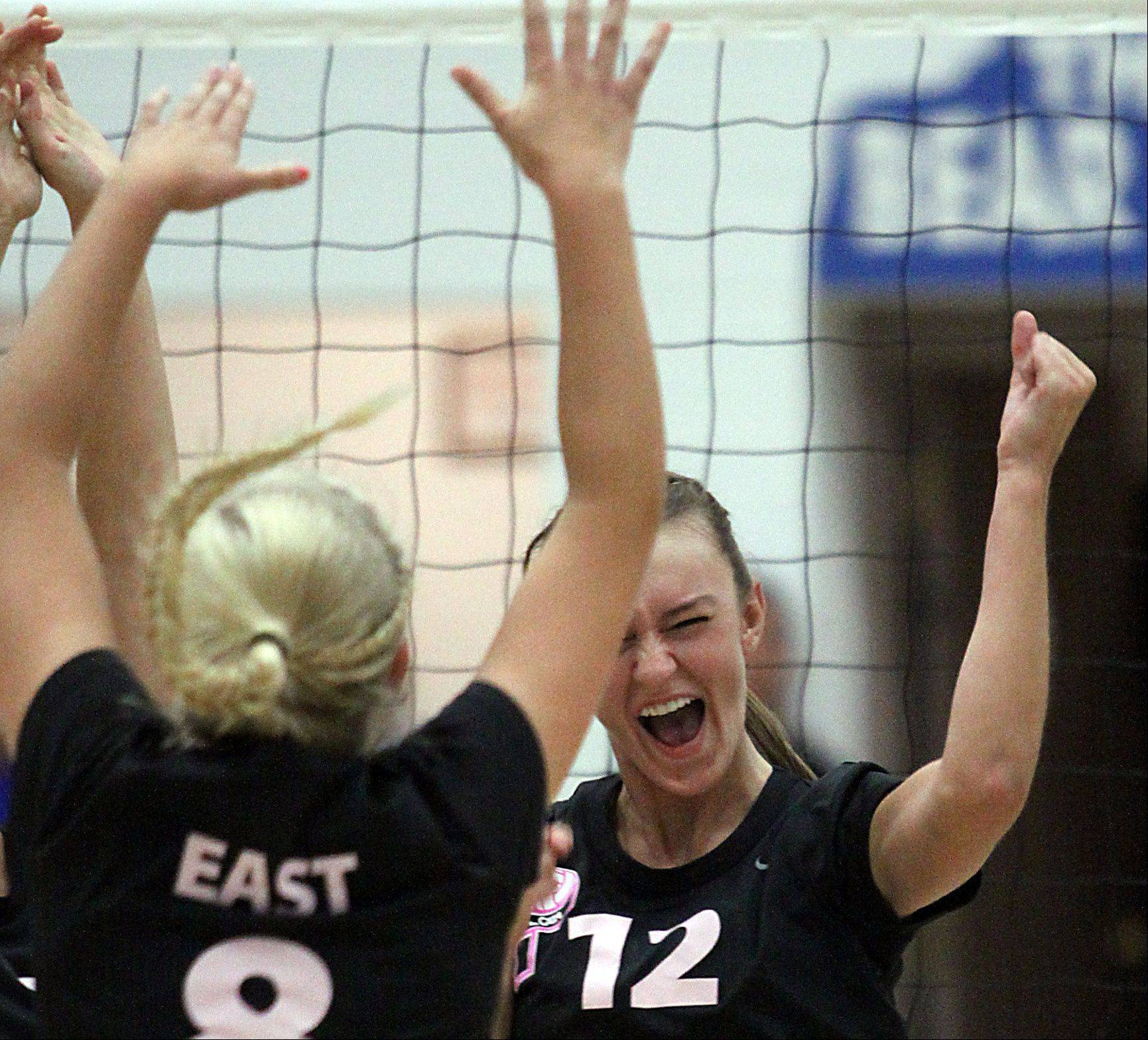 St. Charles East's Ashley Bullock, right, and Chloe Rojas, left, celebrate a point during a varsity volleyball game at St. Charles North on Tuesday evening.