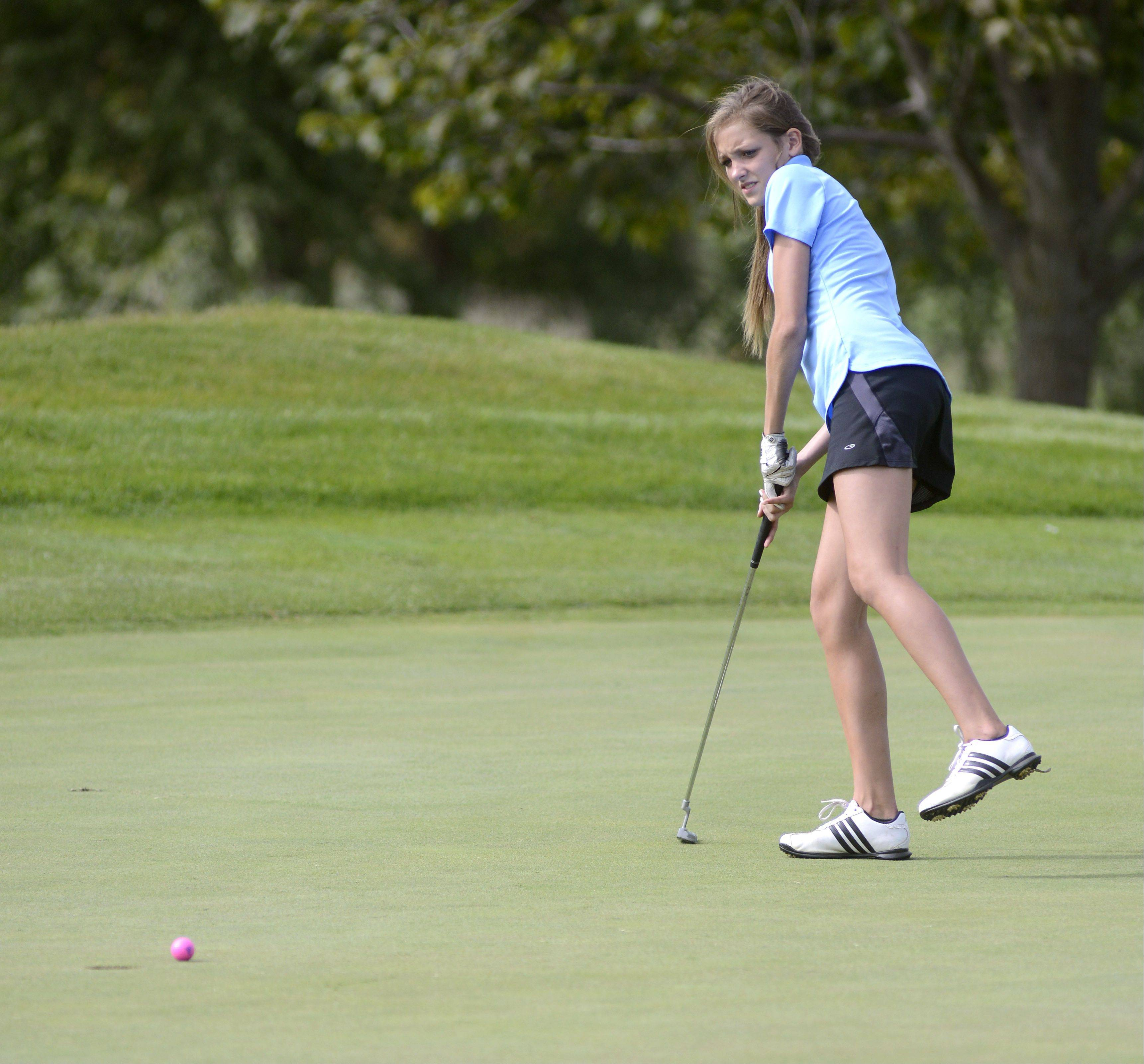Jacobs' Sydney Goll leans over anxiously watching her ball rolling toward the hole on the seventh green of the Prairie course at Boone Creek Golf Club in McHenry on Tuesday.