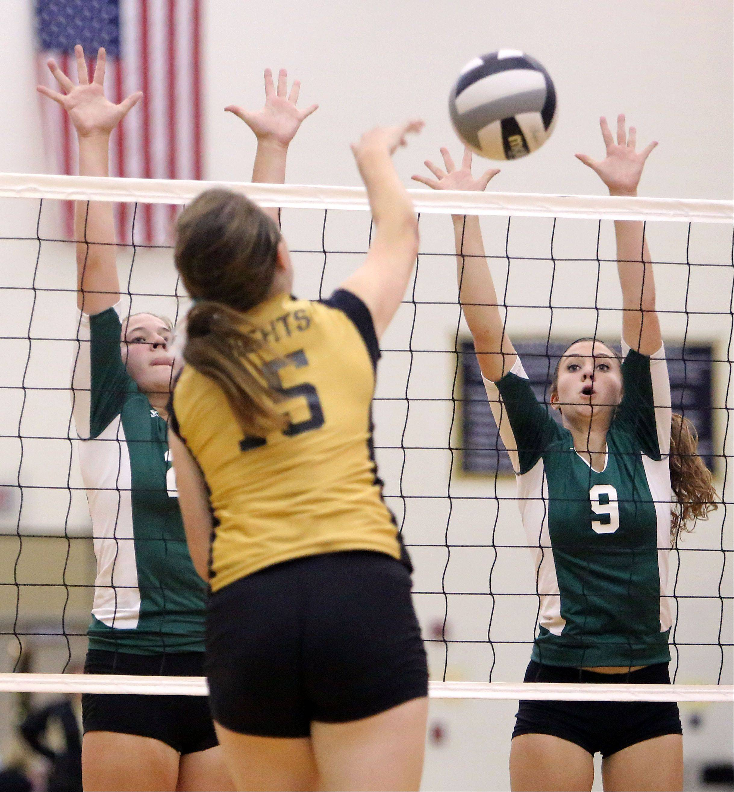 Grayslake North's Nicole LeBaron spikes one at Grayslake Central's Emily Donelly, left, and Anna Basten on Tuesday at Grayslake North.