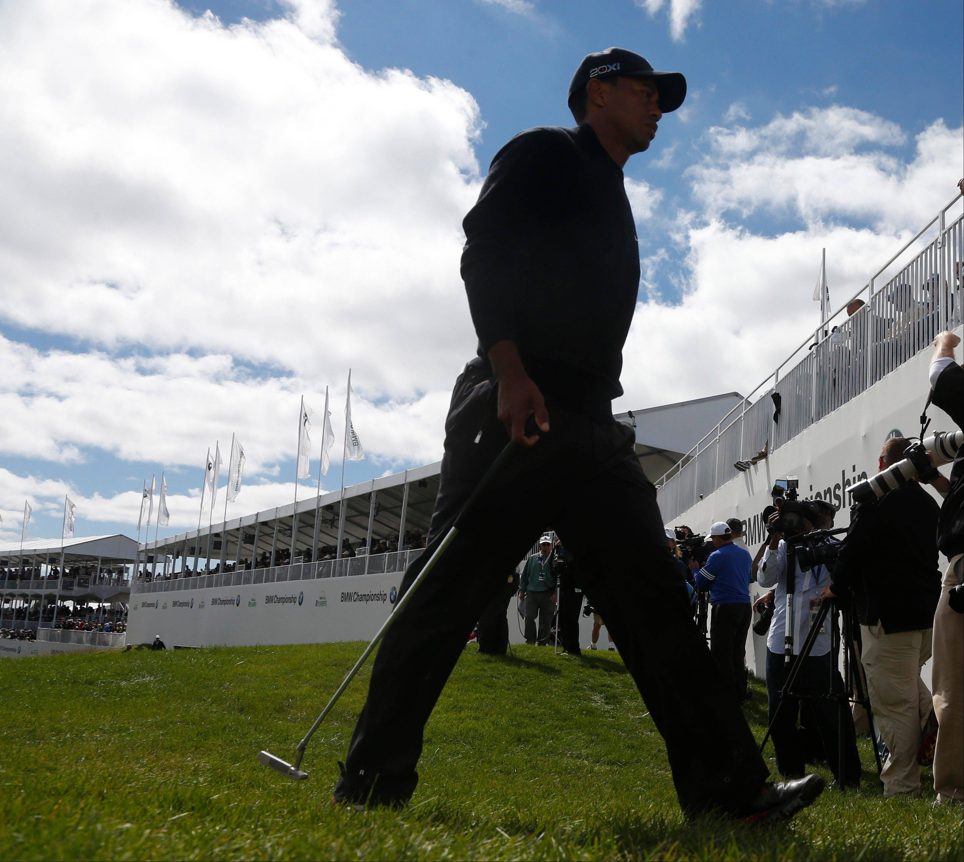 Tiger Woods walks off the 18th green after the final round of the BMW Championship golf tournament at Conway Farms Golf Club in Lake Forest, Ill., Monday, Sept. 16, 2013.