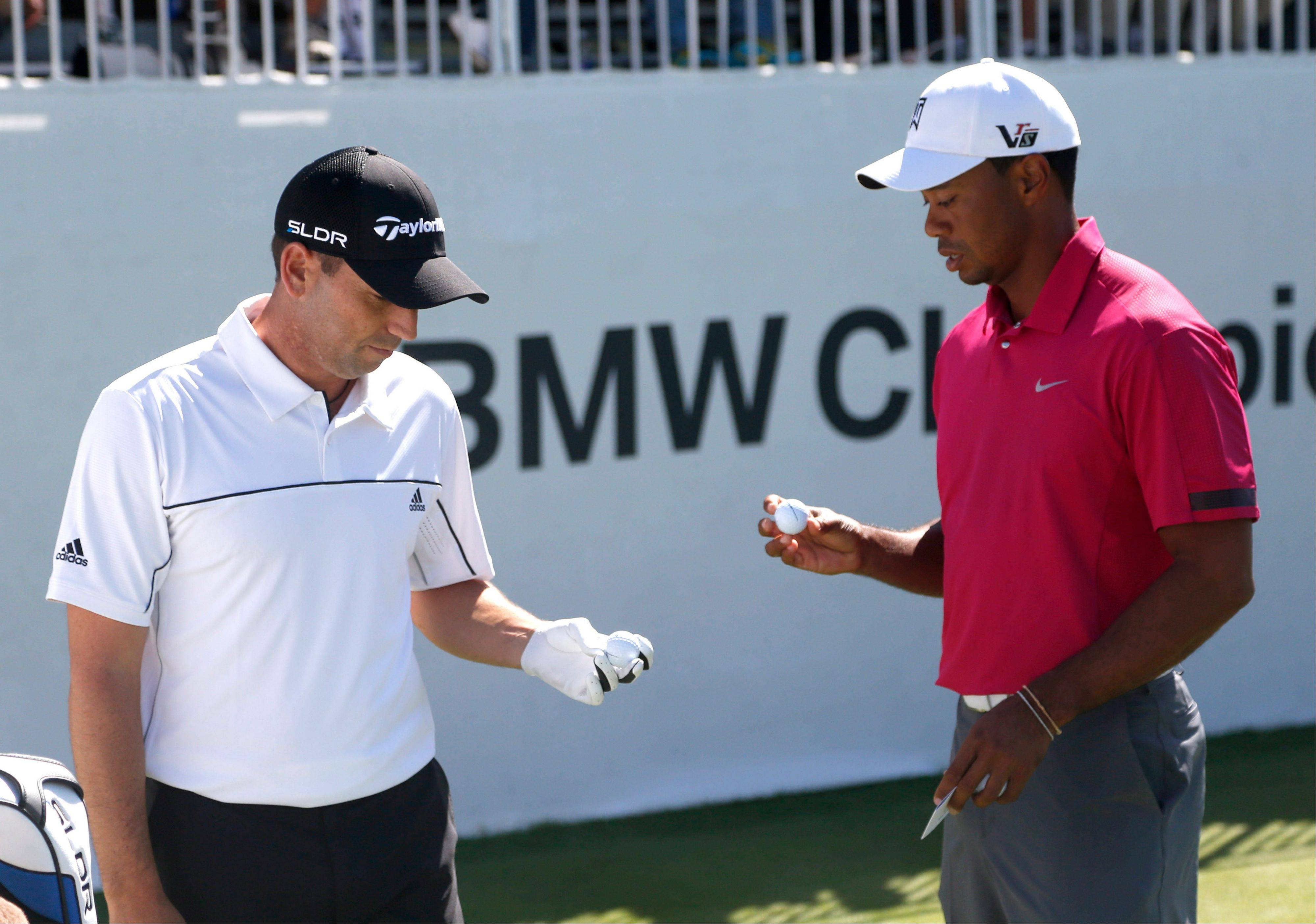 Sergio Garcia, left, and Tiger Woods check their balls during the third round of the BMW Championship golf tournament at Conway Farms Golf Club in Lake Forest, Ill., Saturday, Sept. 14, 2013.