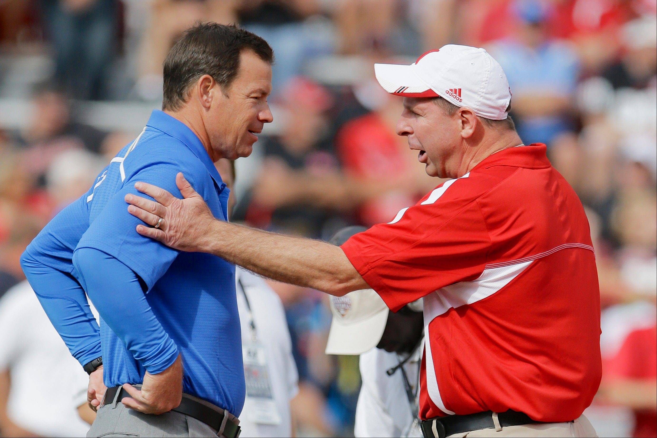 UCLA head coach Jim Mora, left, and Nebraska head coach Bo Pelini meet during warmups prior to an NCAA college football game in Lincoln, Neb., Saturday, Sept. 14, 2013.