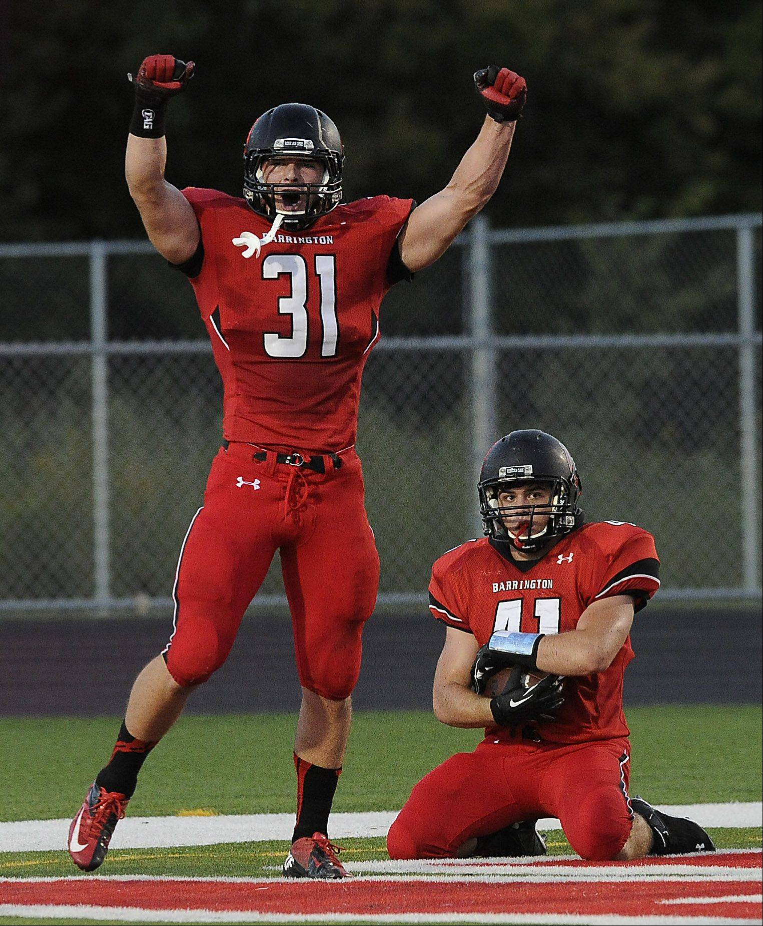 Barrington's Mark Bornhofen recovers a blocked punt as teammate Yovani Romano celebrates the play against Rolling Meadows in Barrington on Thursday.