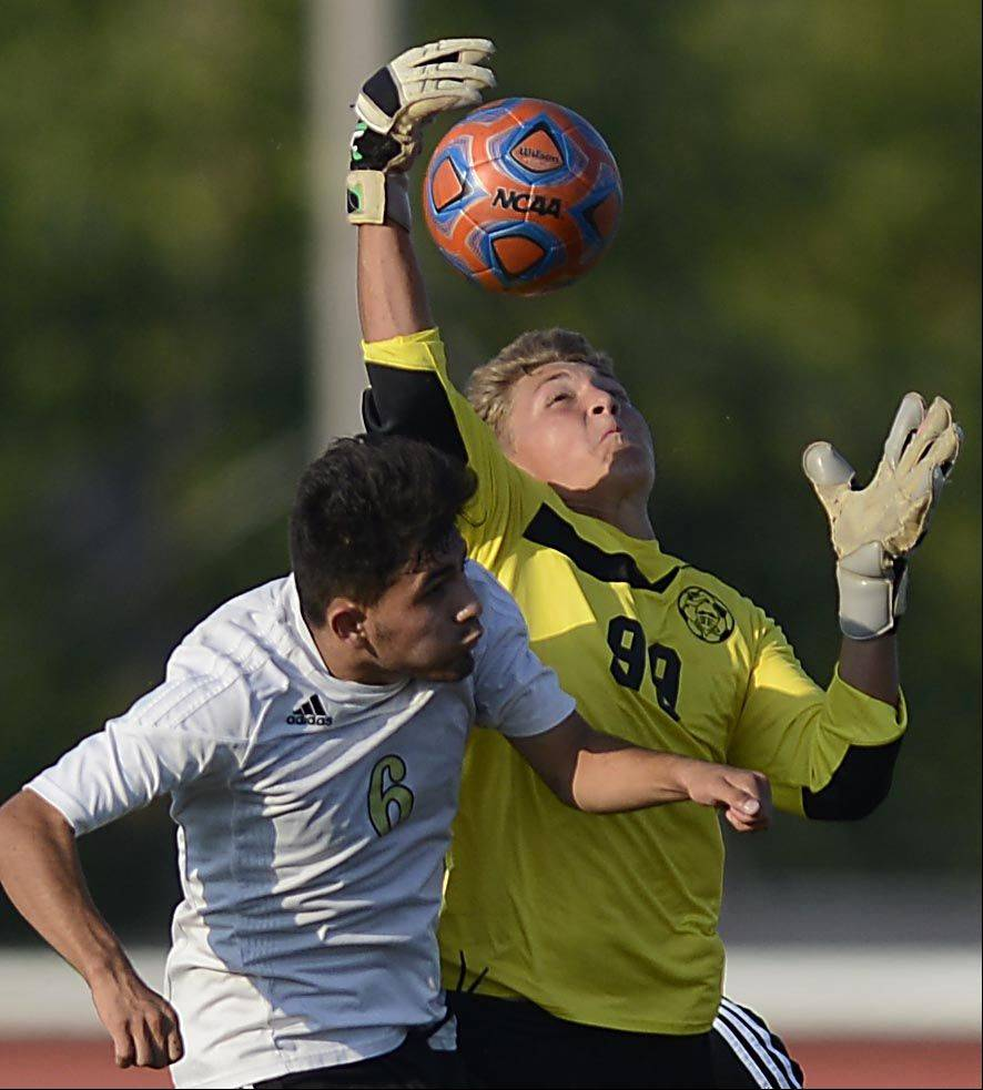 Kaneland's goalkeeper Jarred Karr collects a loose ball against Streamwood's Christian Vences Monday in Streamwood.