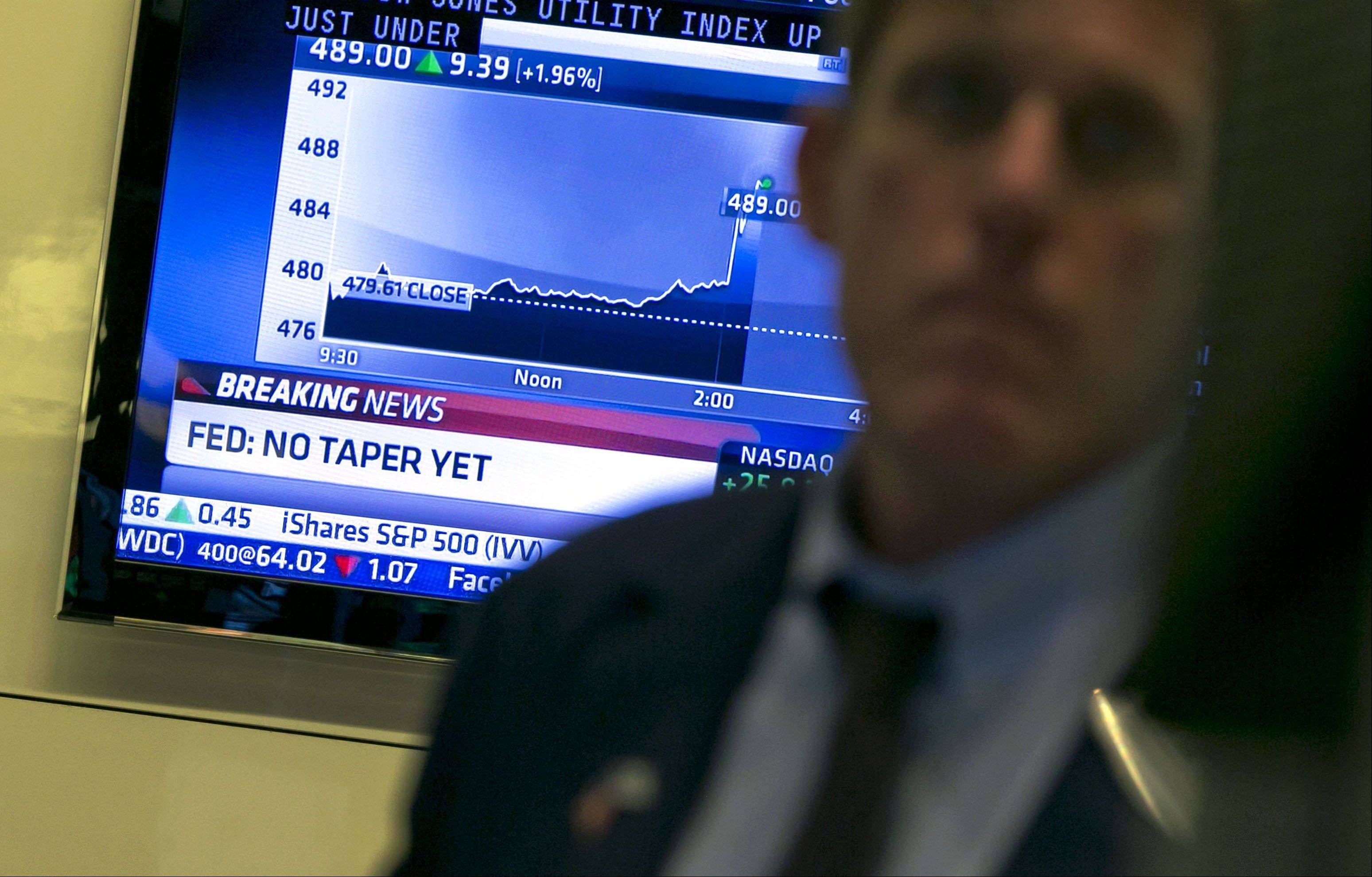 A television monitor on the floor of the New York Stock Exchange shows the decision of the Federal Reserve, Wednesday, Sept. 18, 2013. The Federal Reserve has decided against reducing its stimulus for the U.S. economy, saying it will continue to buy $85 billion a month in bonds because it thinks the economy still needs the support.