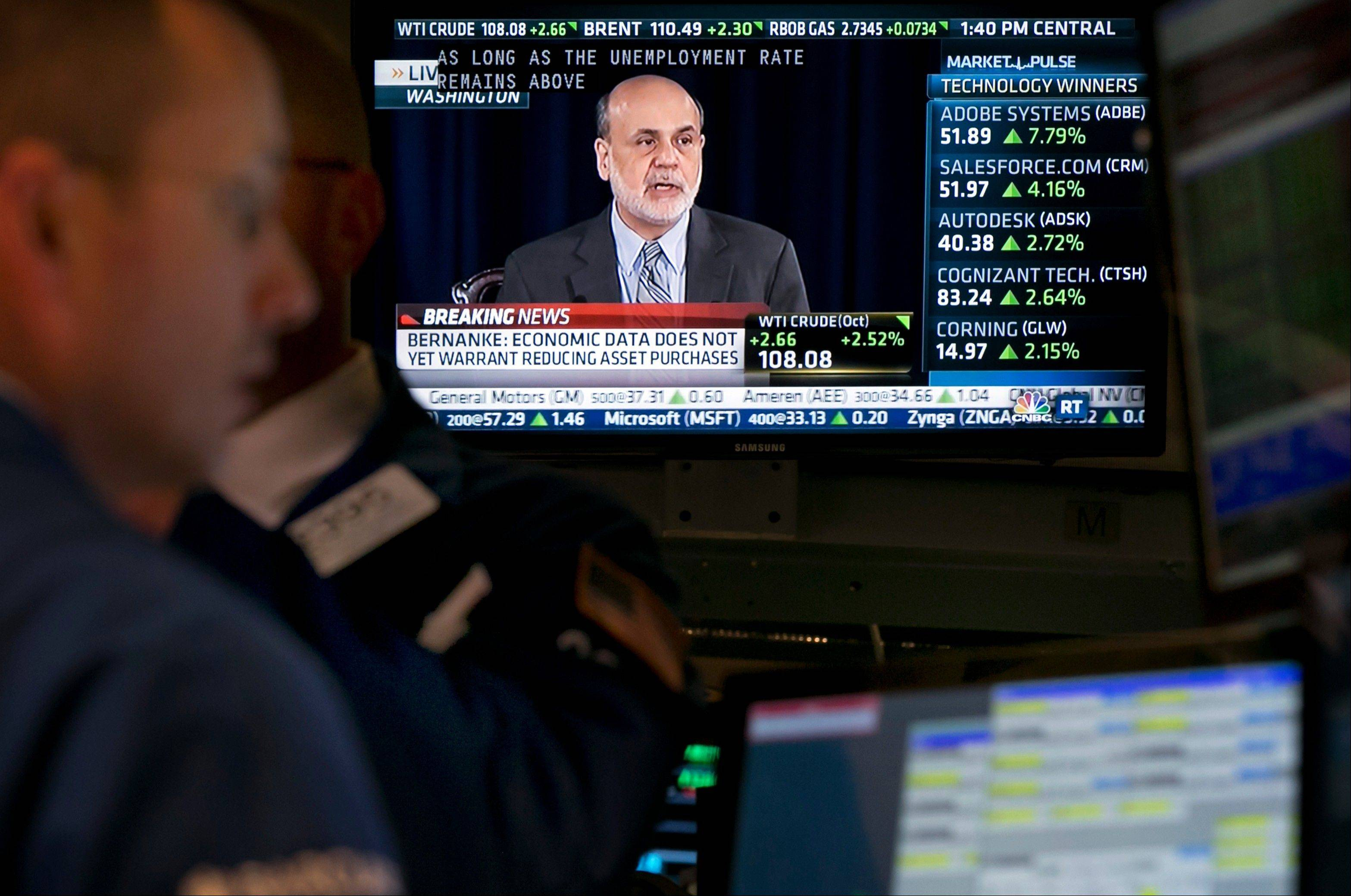 The news conference of Fed Chairman Ben Bernanke appears on a television screen at a post on the floor of the New York Stock Exchange Wednesday. The Federal Reserve decided against reducing its stimulus for the U.S. economy, saying it will continue to buy $85 billion a month in bonds because it thinks the economy still needs the support.