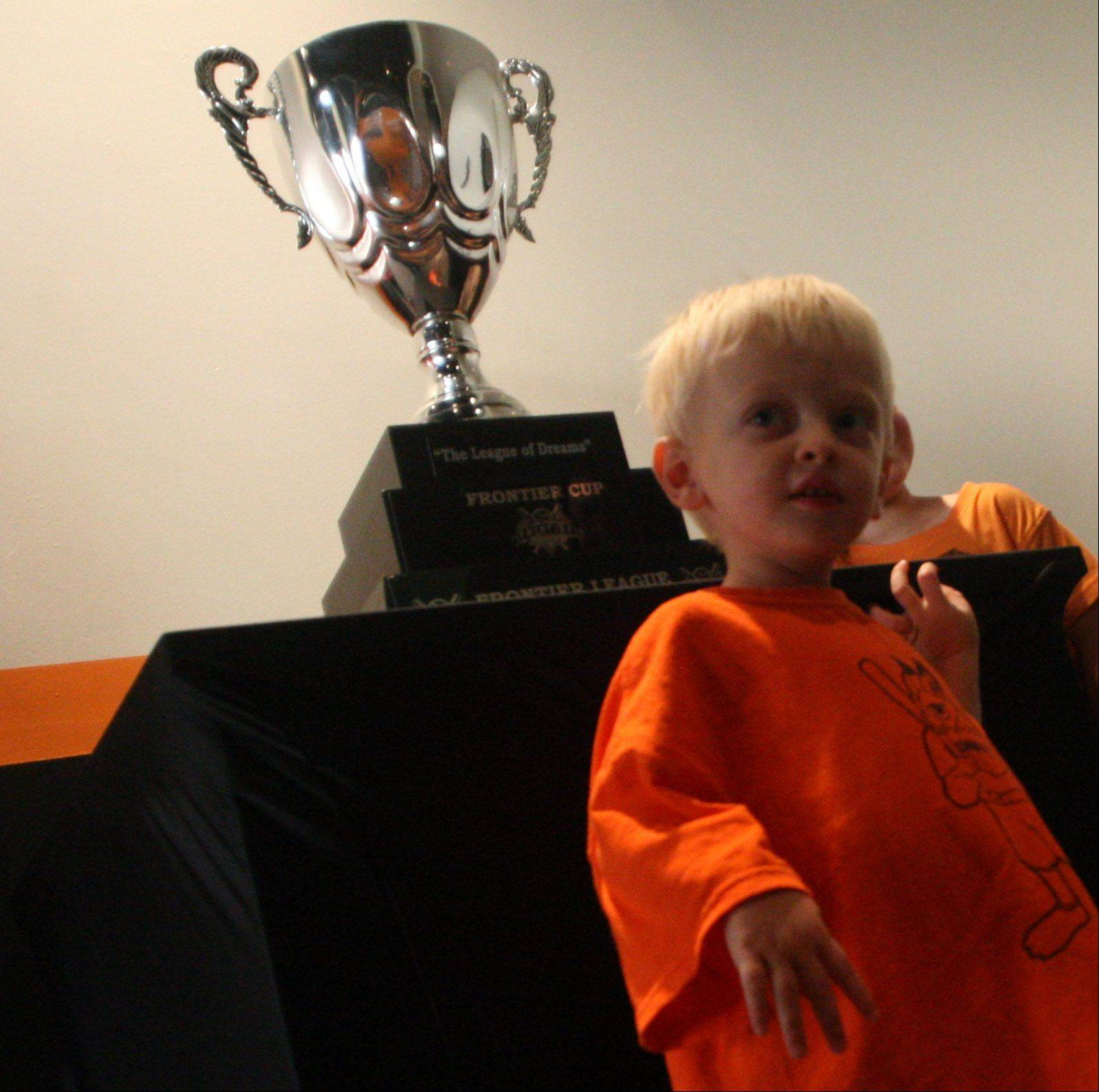 Cooper Matyja, 2, of Hoffman Estates has his picture taken with the Frontier Cup championship trophy as the Boomers arrived home to a reception at Boomers Stadium in Schaumburg on Wednesday.
