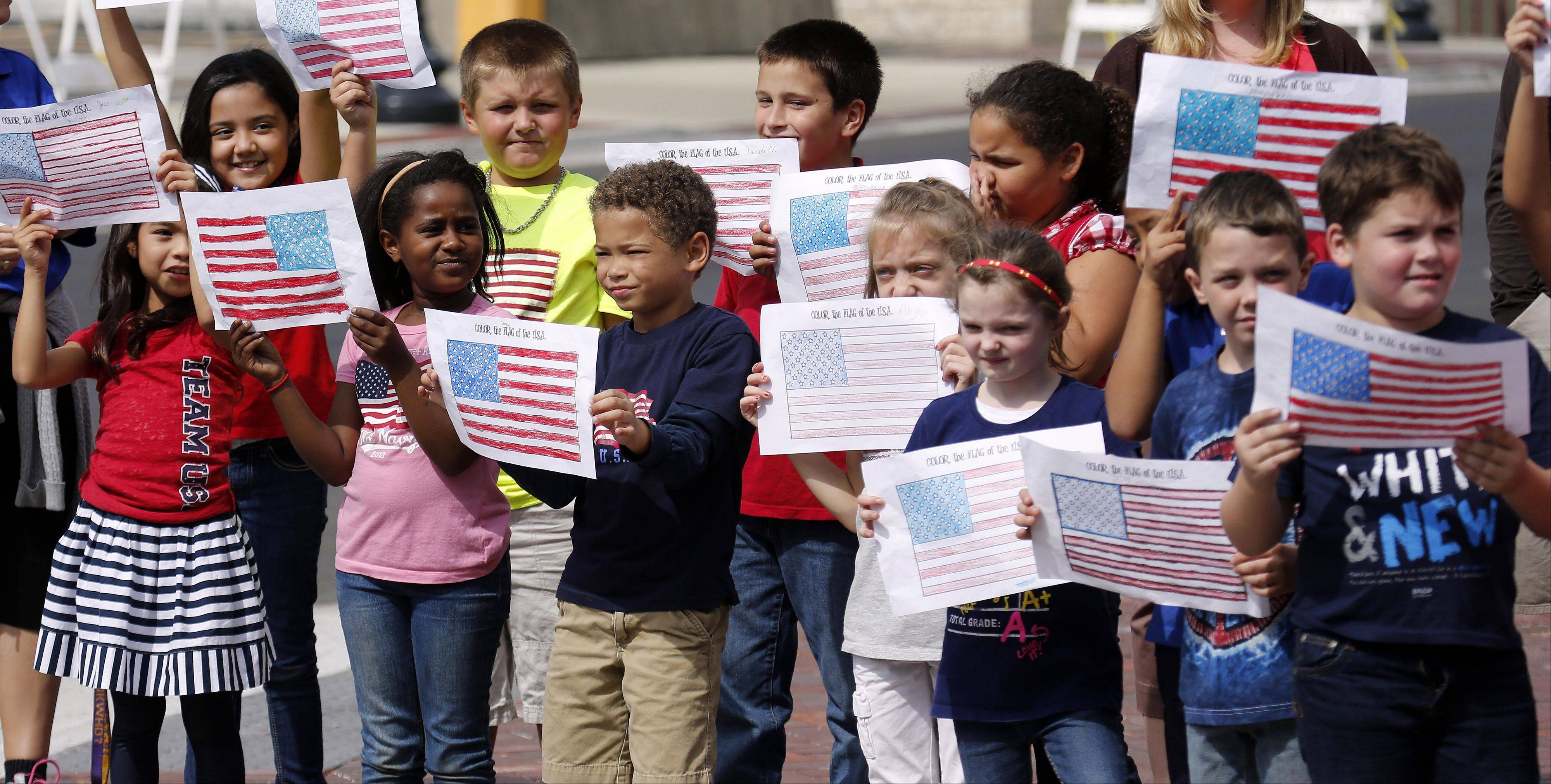 "Students from St. John's Lutheran School in Elgin hold flags Tuesday as ""The Wall That Heals"" travels along Division Street with a motorcycle escort led by the Elgin police and fire departments."