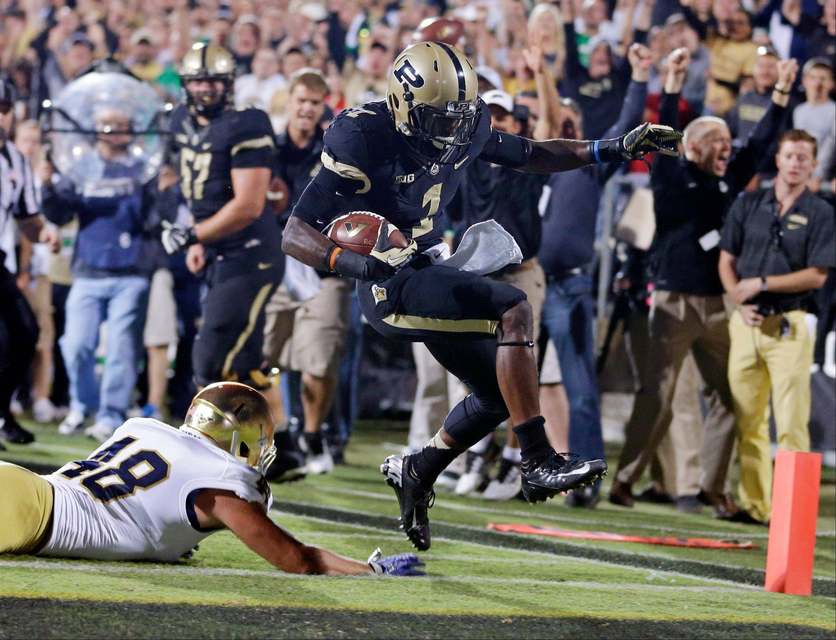 Purdue running back Akeem Hunt, right, goes over Notre Dame linebacker Dan Fox on his way to a touchdown during the first half of Saturday�s game in West Lafayette, Ind. The Boilermakers nearly upset Notre Dame.