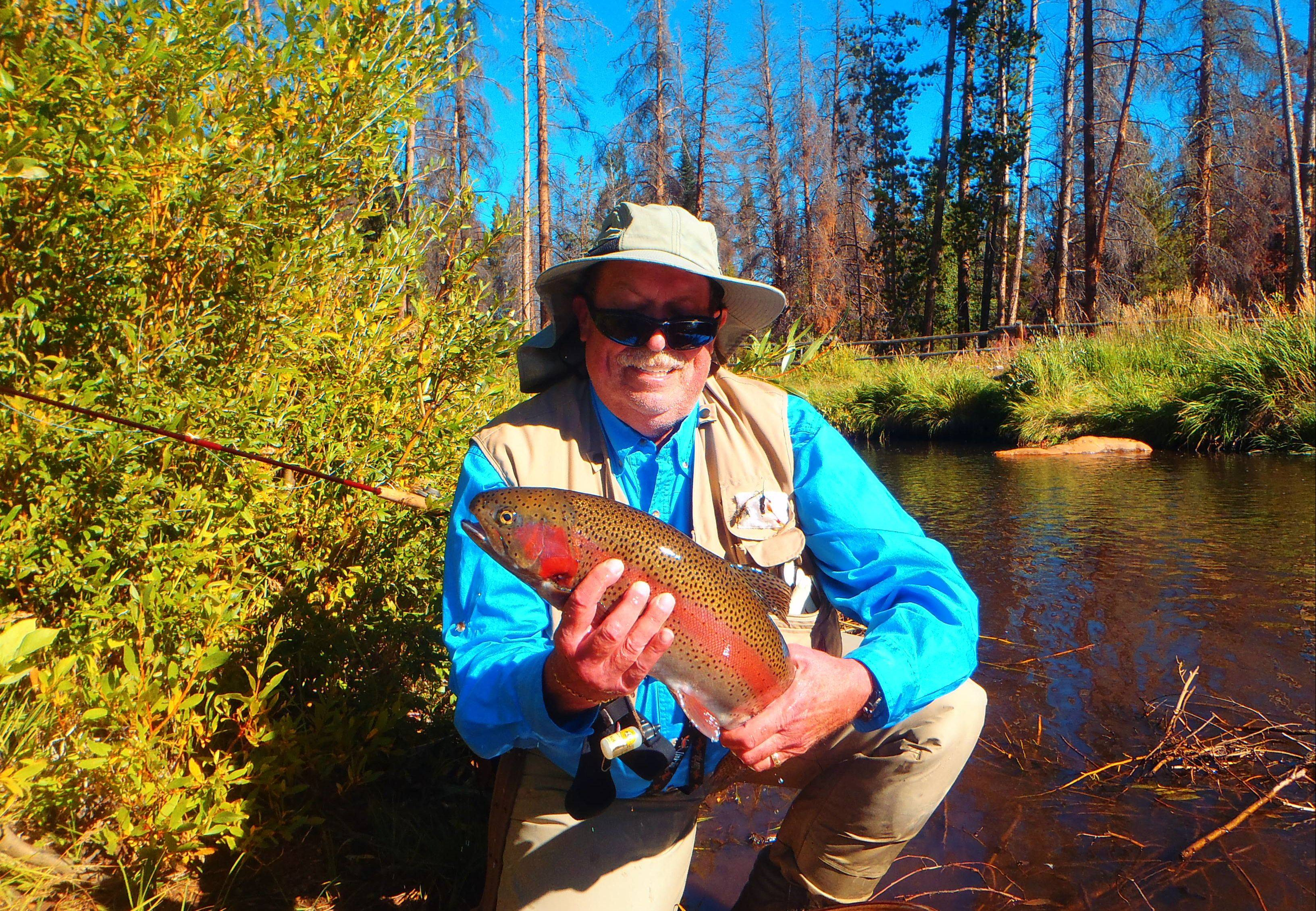 Mike Jackson displays the bounty of Rawah Ranch, a 24-inch rainbow trout he landed in northern Colorado.