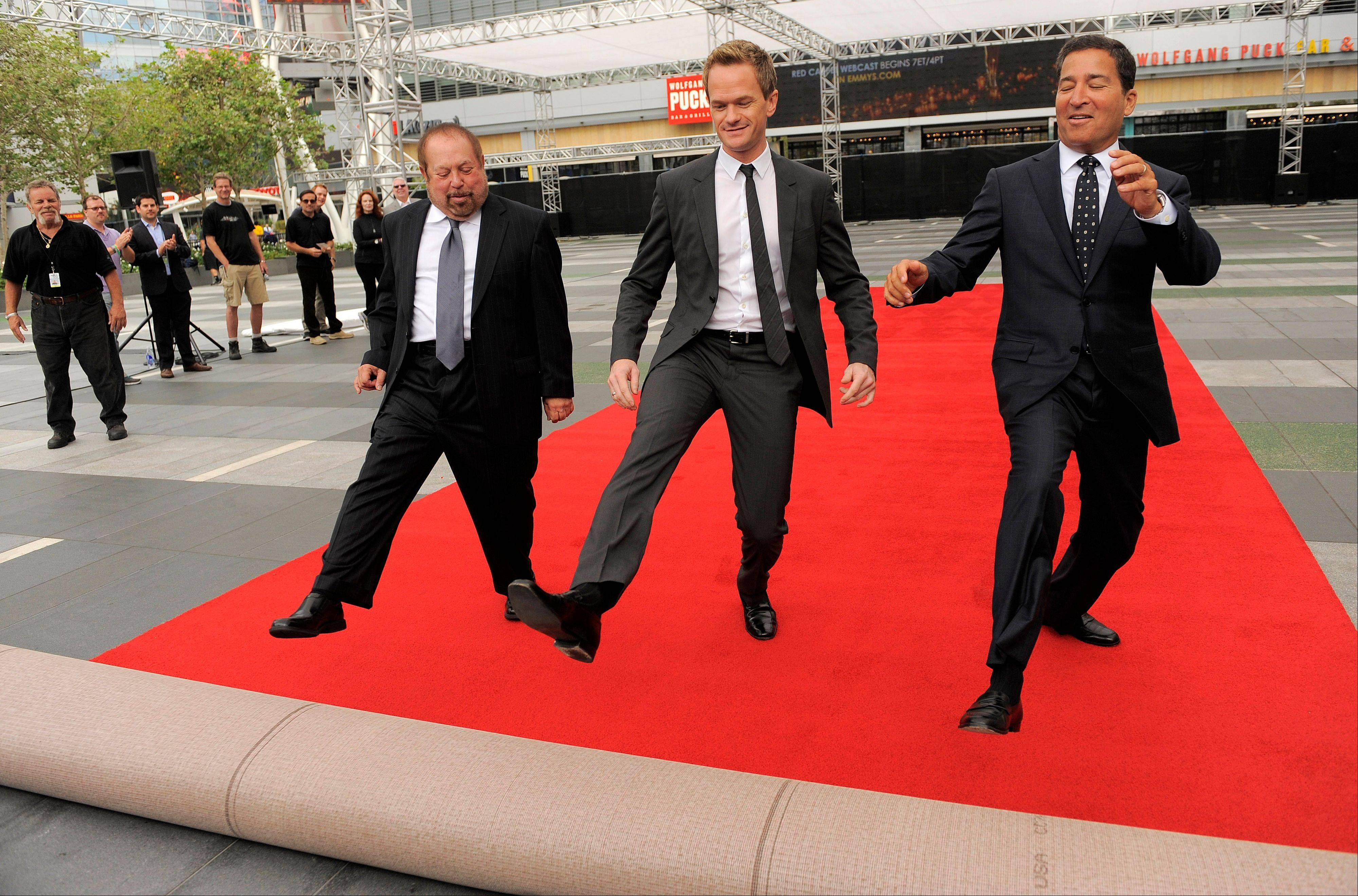 Ken Ehrlich, left, executive producer of Sunday's 65th Emmy Awards telecast, host Neil Patrick Harris, center, and Television Academy Chairman and CEO Bruce Rosenblum roll out the red carpet for the show on Wednesday in Los Angeles.