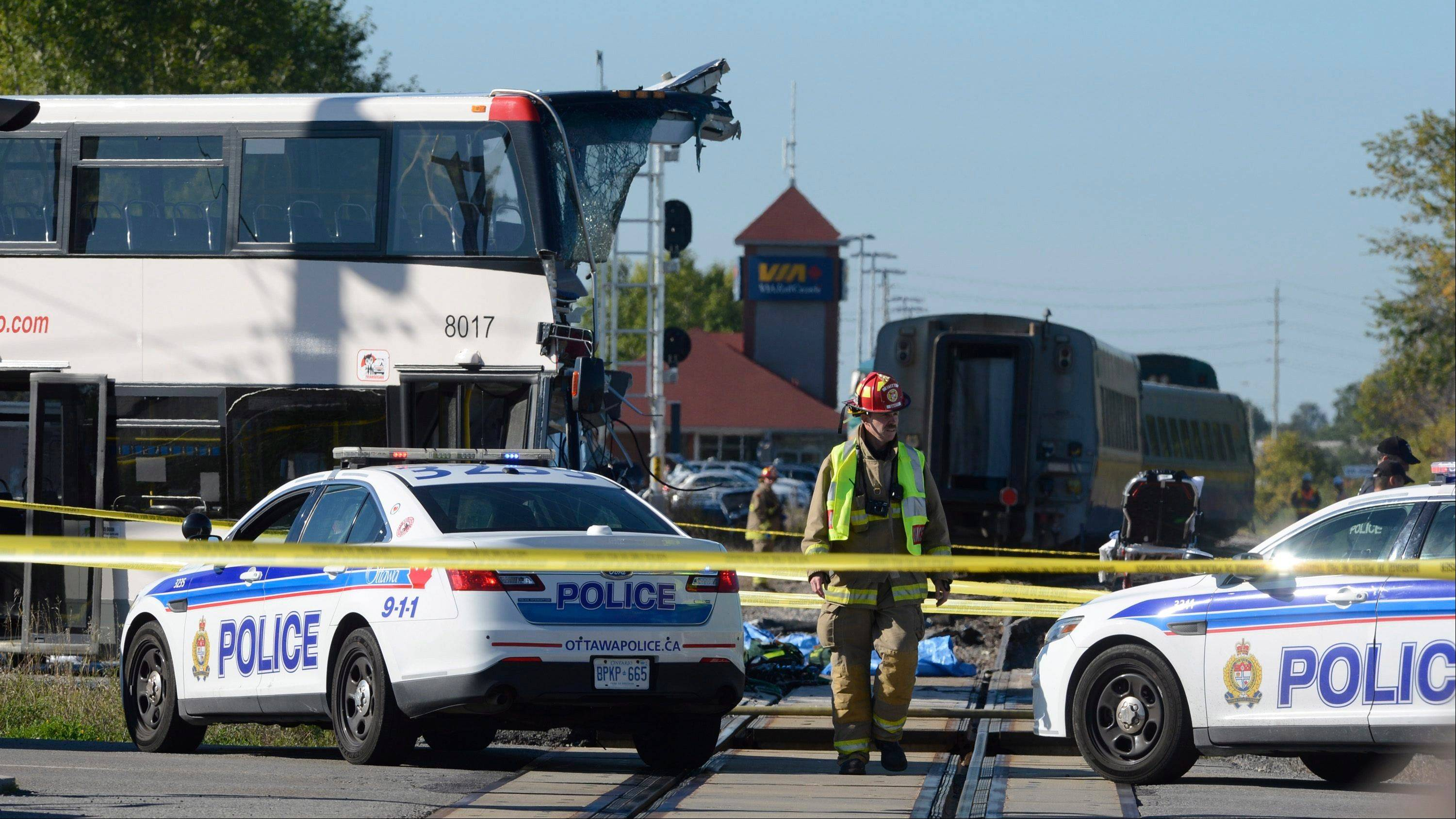 A firefighter surveys the scene of a collision with a train and a city bus in Ottawa, Ontario, Wednesday, Sept. 18, 2013. An Ottawa Fire spokesman said there are �multiple fatalities� and a number of people injured from the bus.